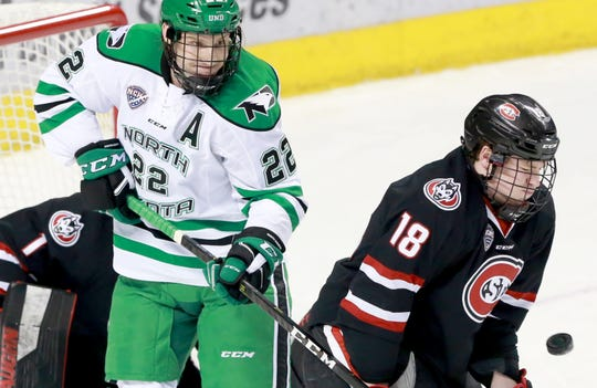 St. Cloud State's Brendan Bushy blocks a Fighting Hawks shot as UND's Rhett Gardner looks for a rebound in Saturday's NCHC game at the Ralph Engelstad Arena.