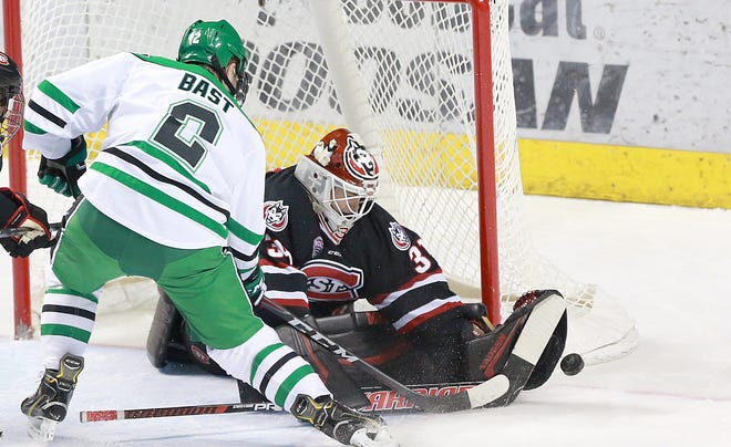 UND's Gabe Bast tries to poke the puck past St. Cloud State goaltender David Hrenak  in Saturday's NCHC game at the Ralph Engelstad Arena.