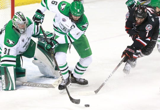 UND's Colton Poolman clears the puck away from  St. Cloud State's Nick Poehling in front of UND goalie Adam Scheel in Saturday's NCHC game at the Ralph Engelstad Arena.