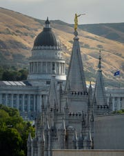 In this July 26, 2017 photo, the angel Moroni statue sits atop the Salt Lake Temple at Temple Square with the Utah State Capitol in the background in Salt Lake City.