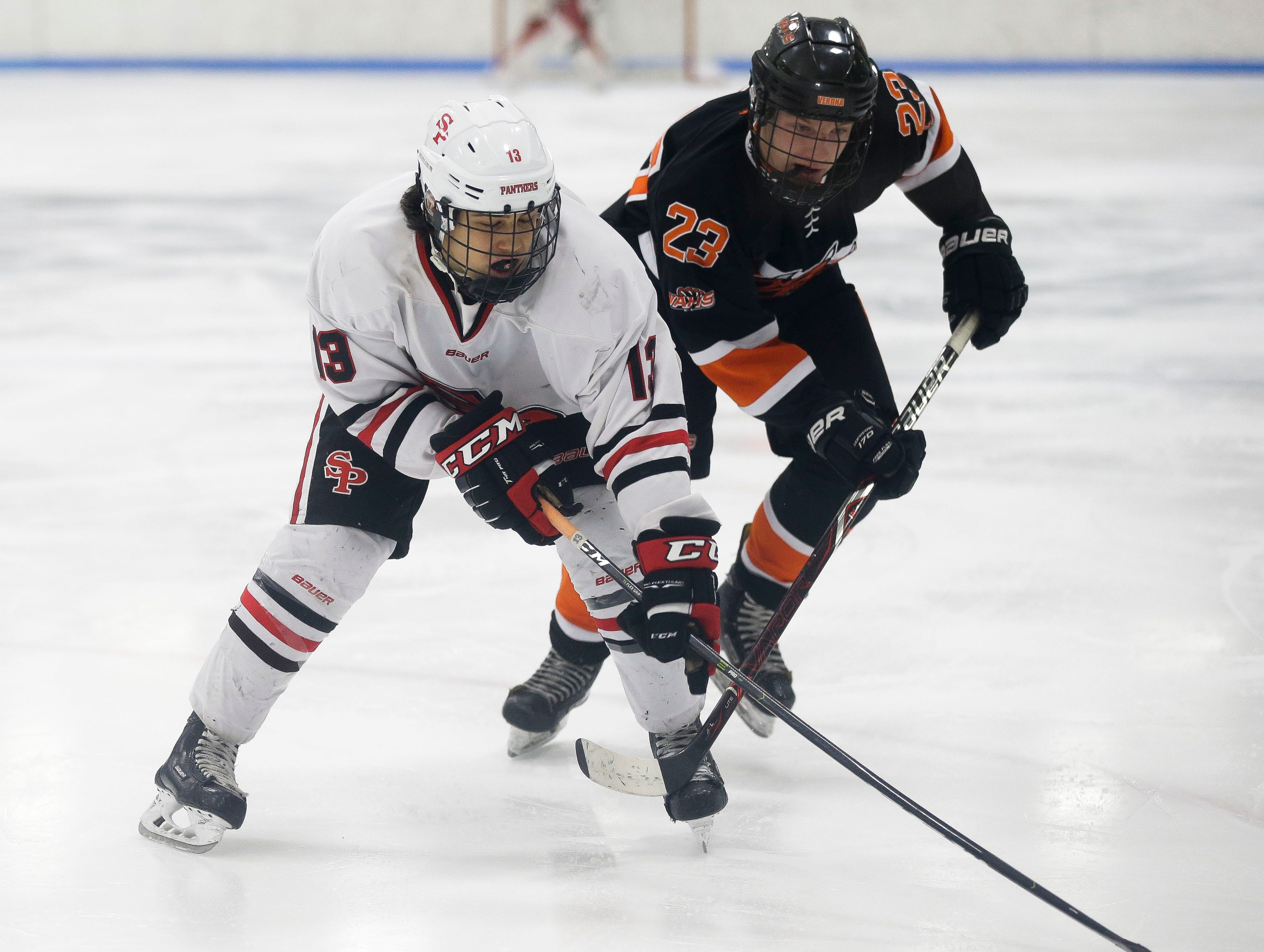 SPASH's Noah Spurlin (13) and Verona's Drew Dingle (23) chase down a loose puck on Saturday, January 26, 2019, at K.B. Willett Ice Arena in Stevens Point, Wis. Tork Mason/USA TODAY NETWORK-Wisconsin