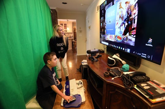 Jack Posnack, 13, plays Fortnite as his mother Robin Fiddle Posnack watches Jan. 23, 2019 at home in New City. Jack has a rare genetic condition called familial dysautonomia that affects his autonomic nervous system. The virtual world from video games gives him a chance to connect with other kids and make friends. He is raising money to gift another kid the same gaming system.