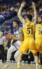 Delaware's Eric Carter tries to get the basket around Drexel's James Butler in the Blue Hens' 76-75 win at the Bob Carpenter Center Saturday.