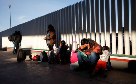 A man sits with his children as they wait to hear if their number is called to apply for asylum in the United States, at the border, Friday, Jan. 25, 2019, in Tijuana, Mexico. The Trump administration on Friday will start forcing some asylum seekers to wait in Mexico while their cases wind through U.S. courts, an official said, launching what could become one of the more significant changes to the immigration system in years. (AP Photo/Gregory Bull)