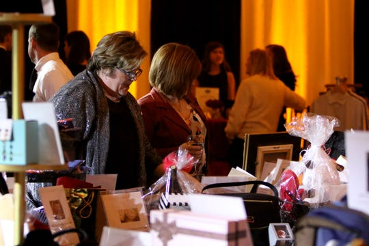 Attendees browse items at the silent auction at Christ Academy's 5th Annual Chocolate Soiree Friday, Jan. 25, 2019, at the Country Club.