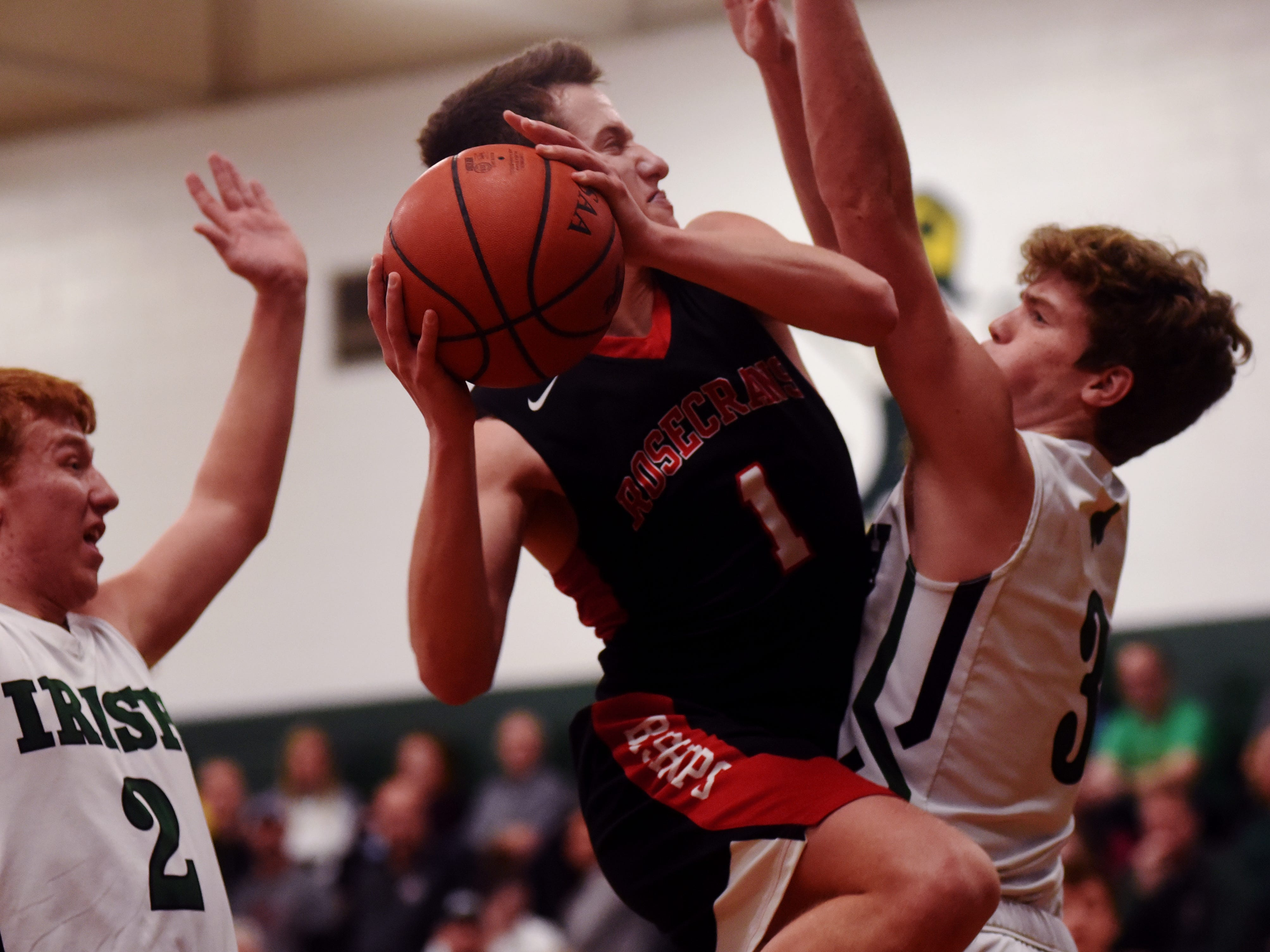Rosecrans' Jack Goggin drives into traffic against Fisher Catholic's Jayden Boyden, left, and Collin McCrady.