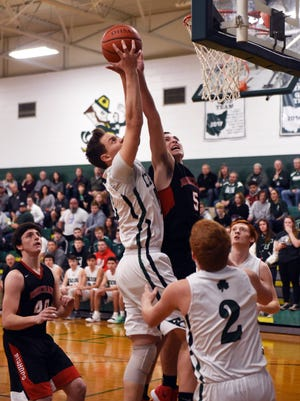 Fisher Catholic's Bailey Francis, left, and Rosecrans' Marcus Browning go up for a rebound during the first quarter of the Bishops' 55-47 win on Saturday night in Lancaster.