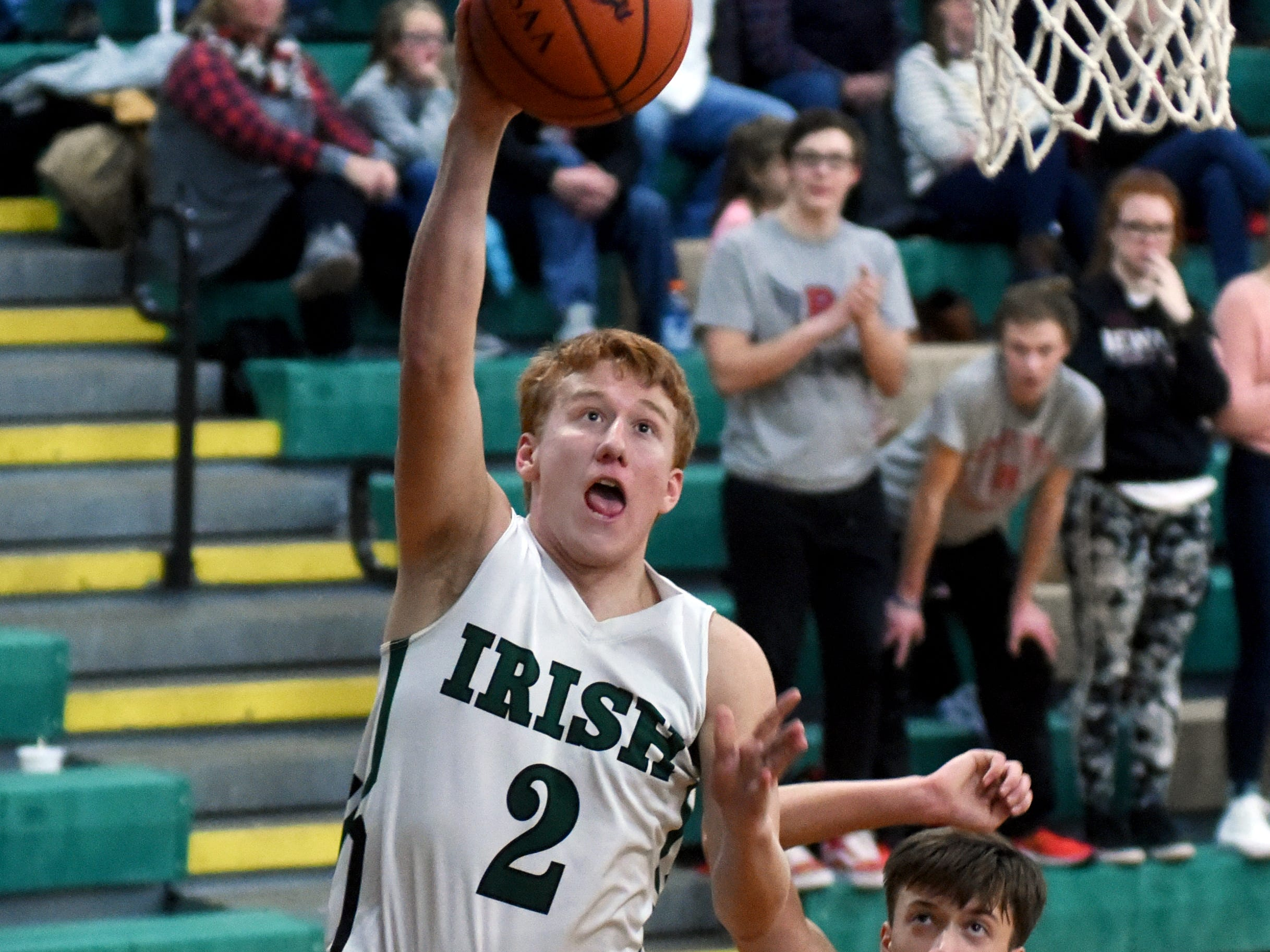 Jayden Boyden goes in for a layup over Josh Merva during the second half of Fisher Catholic's 55-47 loss to visiting Rosecrans on Saturday night in Lancaster.