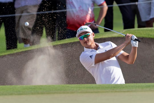 Haotong Li of China chips out of a bunker on the 14th hole during the final round of the Dubai Desert Classic.