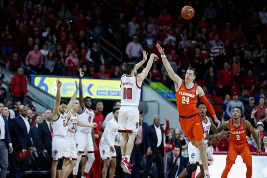 Jan 26, 2019; Raleigh, NC, USA; North Carolina State guard Braxton Beverly (10) shoots a 3-pointer over Clemson Tigers forward David Skara (24) as time expires in the second half at PNC Arena.