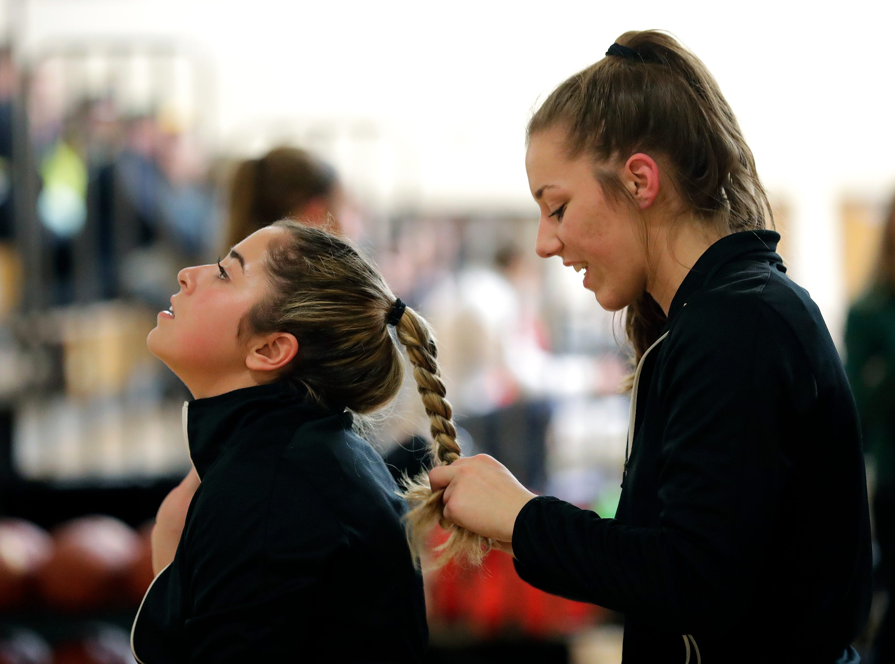 Freedom High School's Claire Burton, left, has her hair braided by Taylor Haase prior to playing against Luxemburg-Casco High School during their girls basketball game Thursday, January 24, 2019, in Freedom, Wis. 