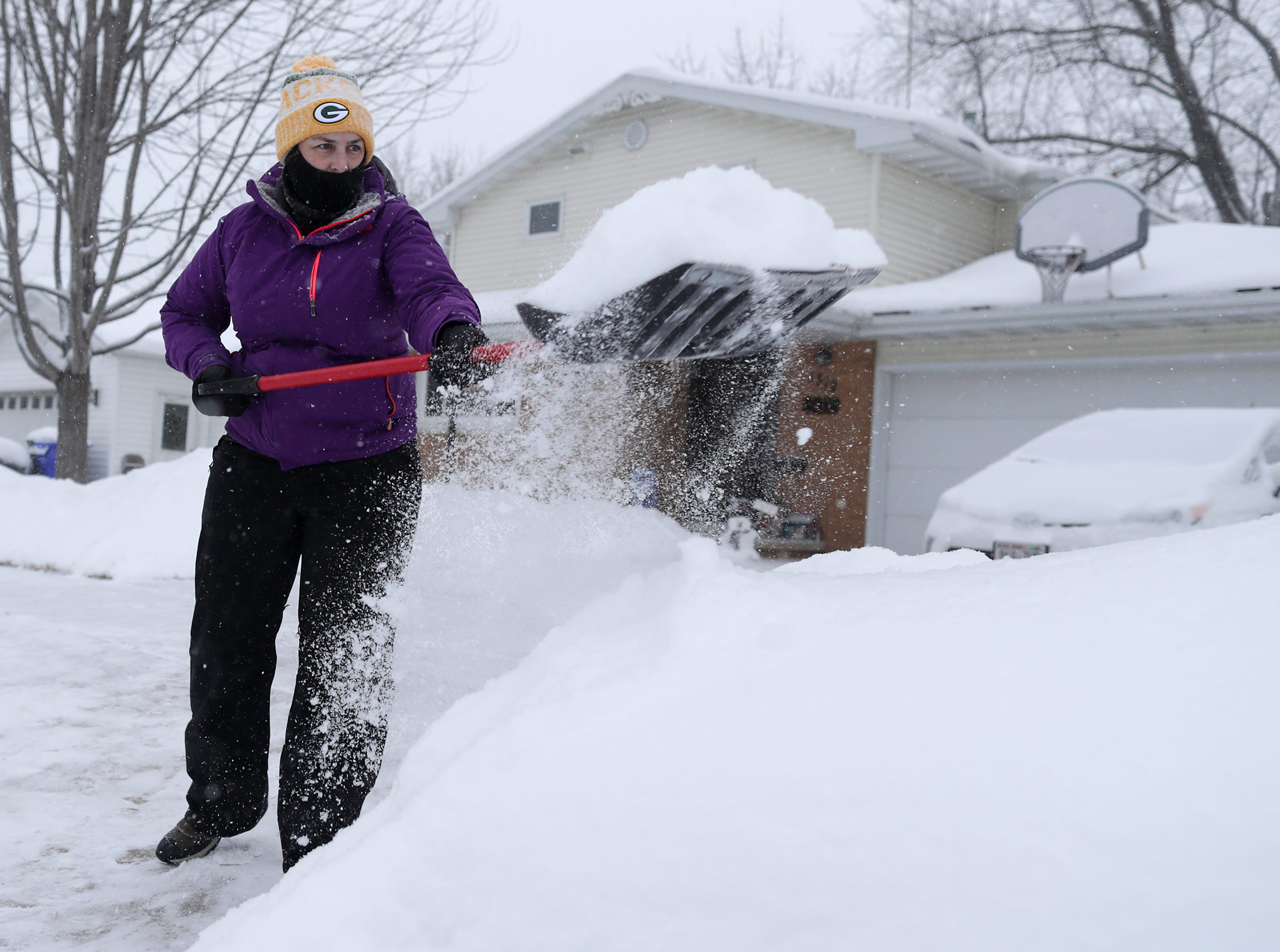 Kris Kandler shovels during a winter storm in Wisconsin on Monday, January 28, 2019, in Kaukauna, Wis.