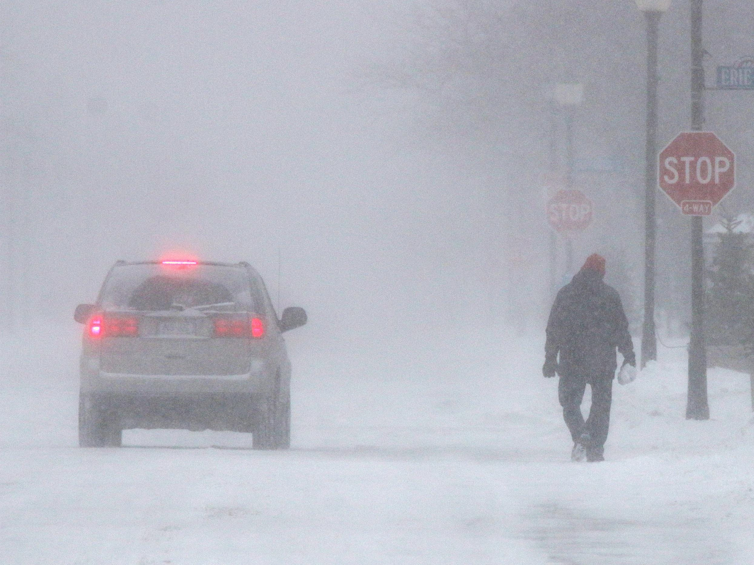 A man walks on the road in near whiteout conditions, on Erie and North Eighth Street, Monday, Jan. 28, 2019, in Sheboygan, Wis.