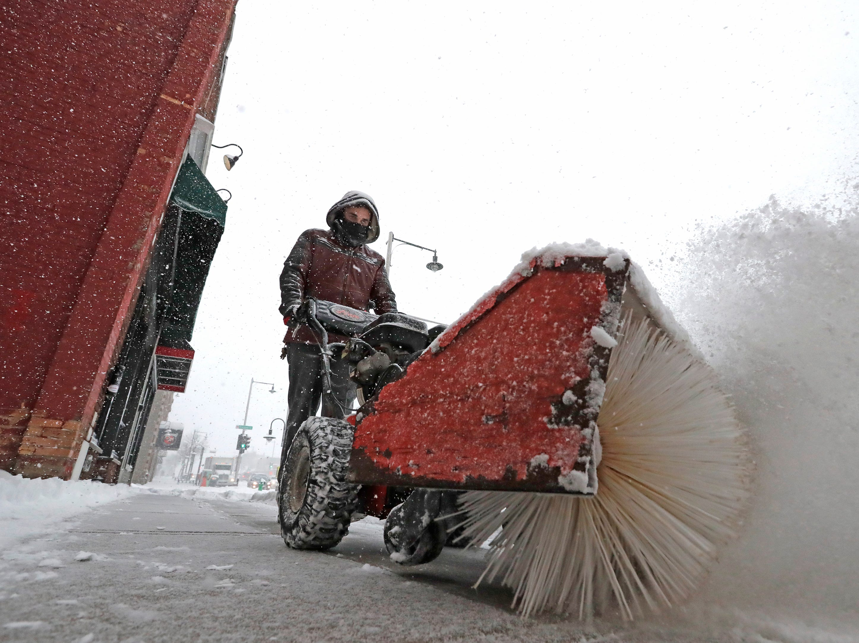 Ben Salzman, an employee with Red Lion Hotel Paper Valley, clears snow from in front of the hotel during a snowstorm Wednesday, January 23, 2019, in downtown Appleton, Wis. 