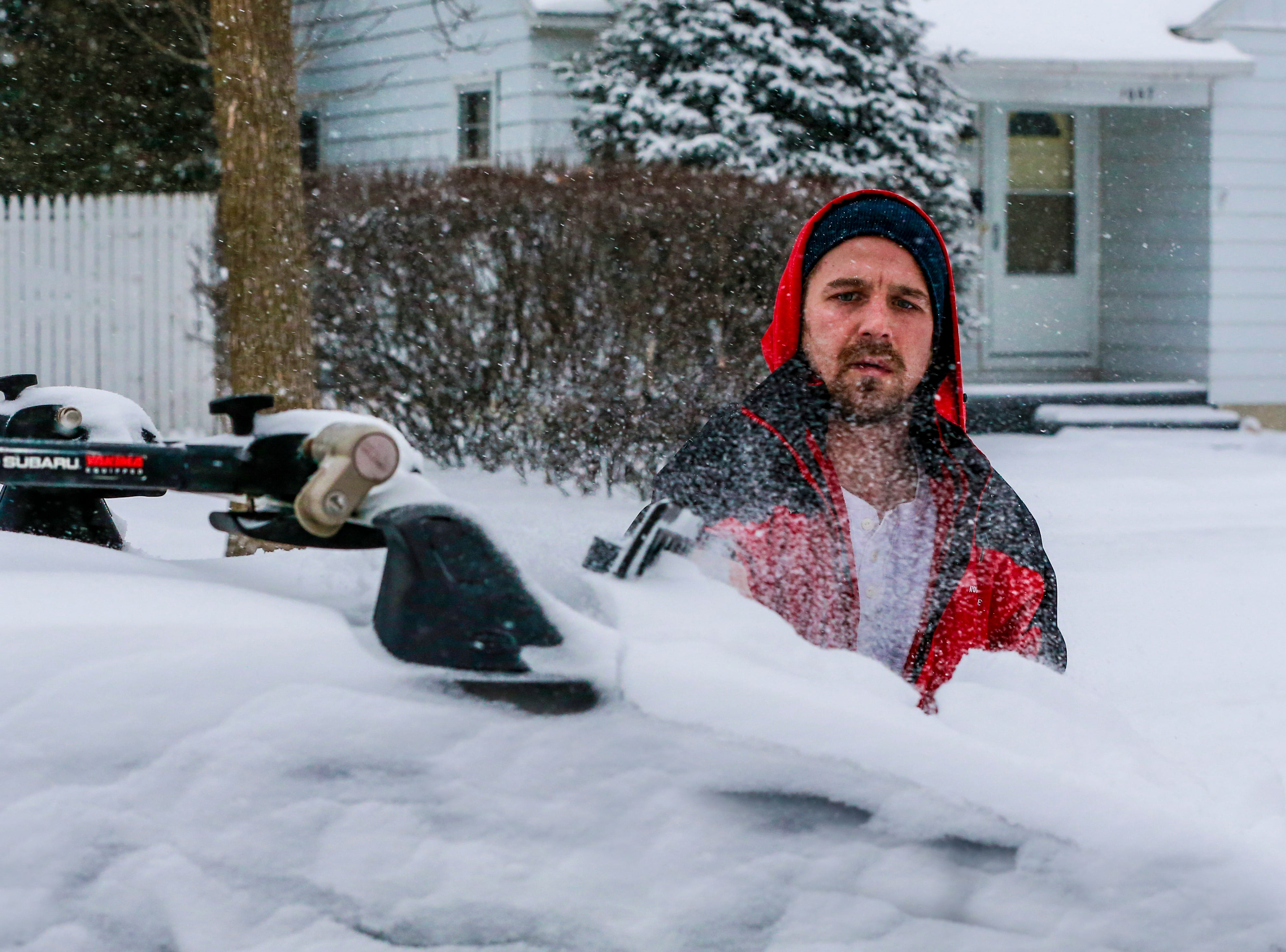 Cody Harmon brushes off snow that covered his vehicle after a snowstorm Monday, Jan. 28, 2019, in Wausau, Wis.