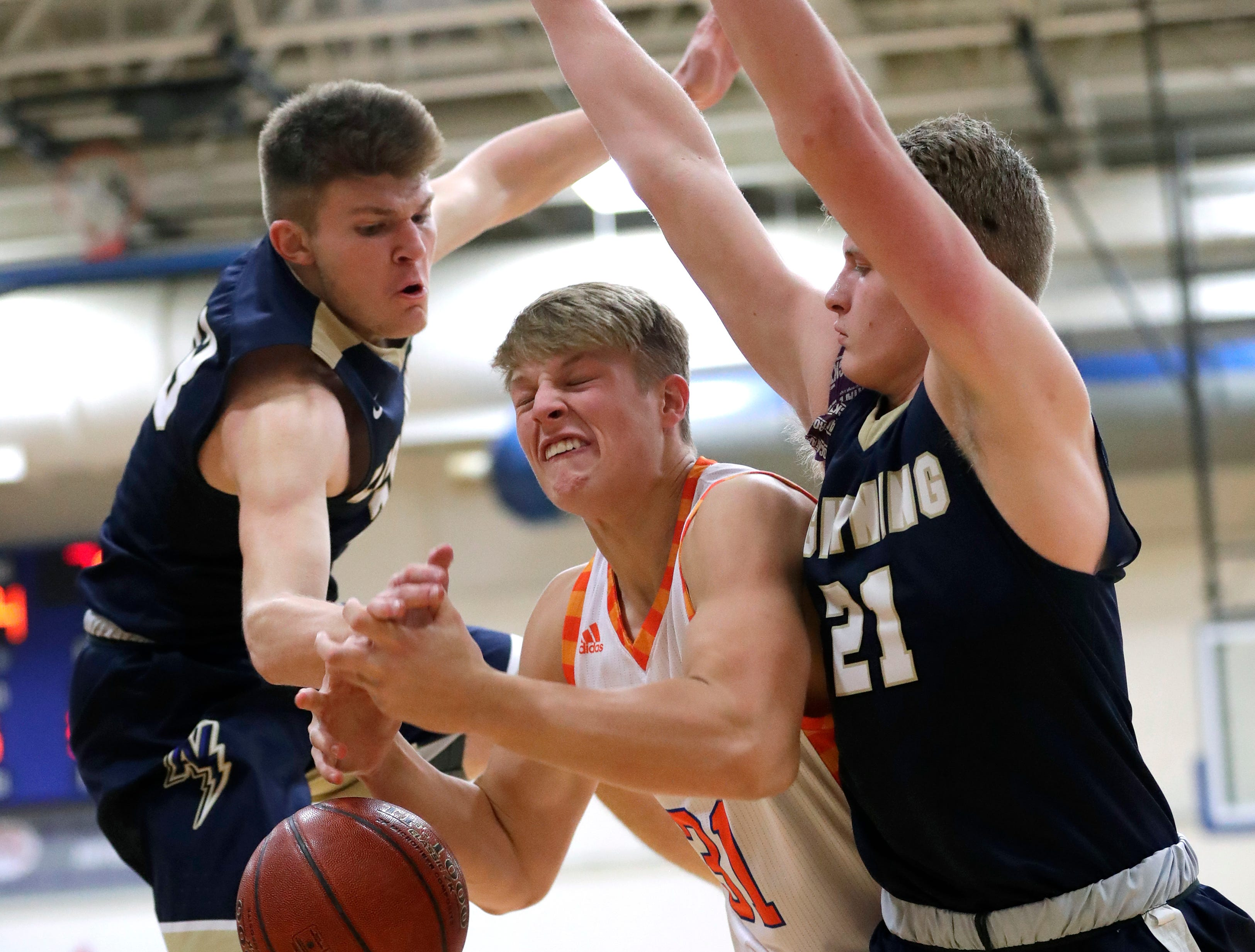 Appleton North High School's Devin Blom, left, and Luke Van Handel, right, defend against Appleton West High School's Sam Pitz during their boys basketball game Friday, January 25, 2019, at Appleton West High School in Appleton, Wis. 