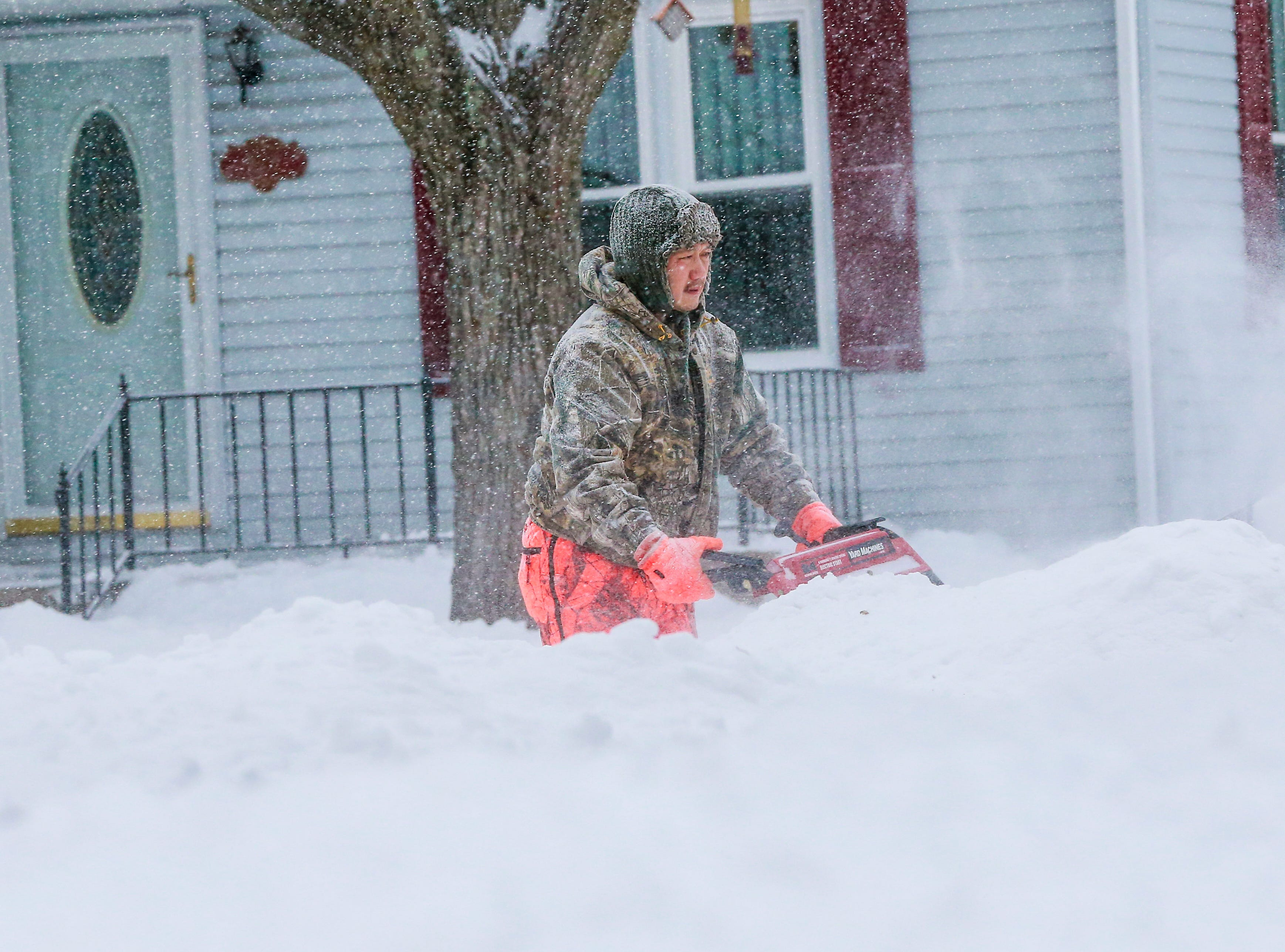 Kangshoua Her clearing snow on his sidewalk after a snowstorm Monday, Jan. 28, 2019, in Wausau, Wis.