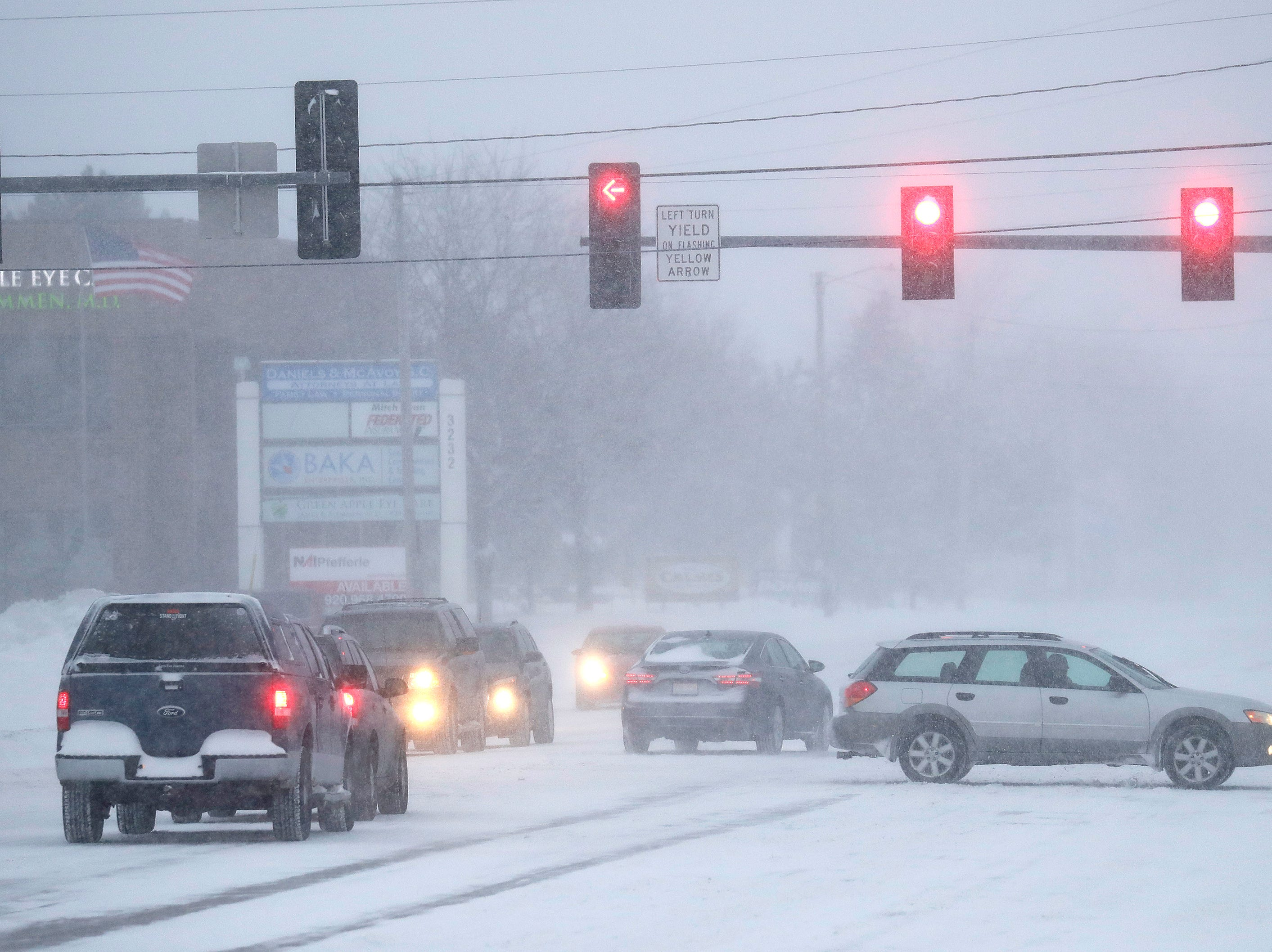 Traffic moves slowly at the corner of E. Capital Drive and Ballard Road during a snowstorm Monday, Jan. 28, 2019, in Appleton, Wis.