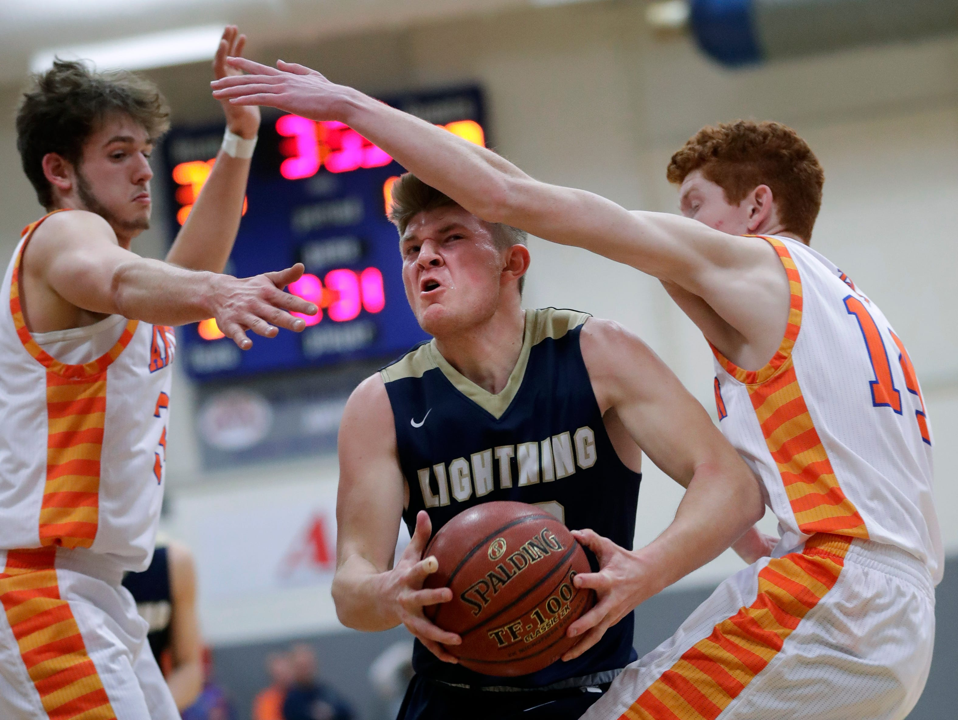 Appleton West High School's Spencer Mellberg, left, and Colin Murray, right, defend against Appleton North High School's Devin Blom as he drives to the basket during their boys basketball game Friday, January 25, 2019, at Appleton West High School in Appleton, Wis. 