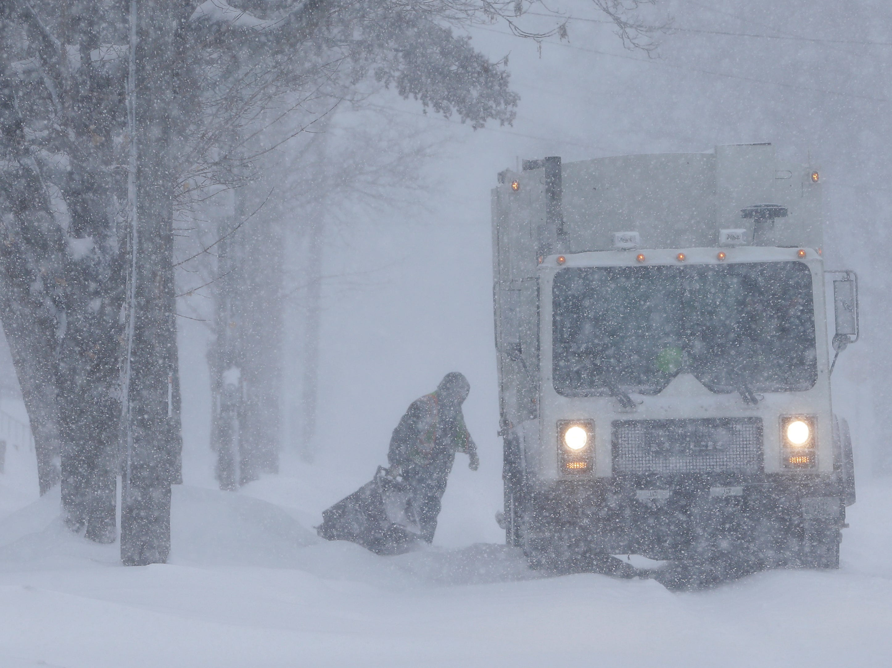 An employee of Pozorski Hauling & Recycling collects trash during a snowstorm on the 1100 block of 13th Street on Monday, Jan. 28, 2019, in Manitowoc, Wis.