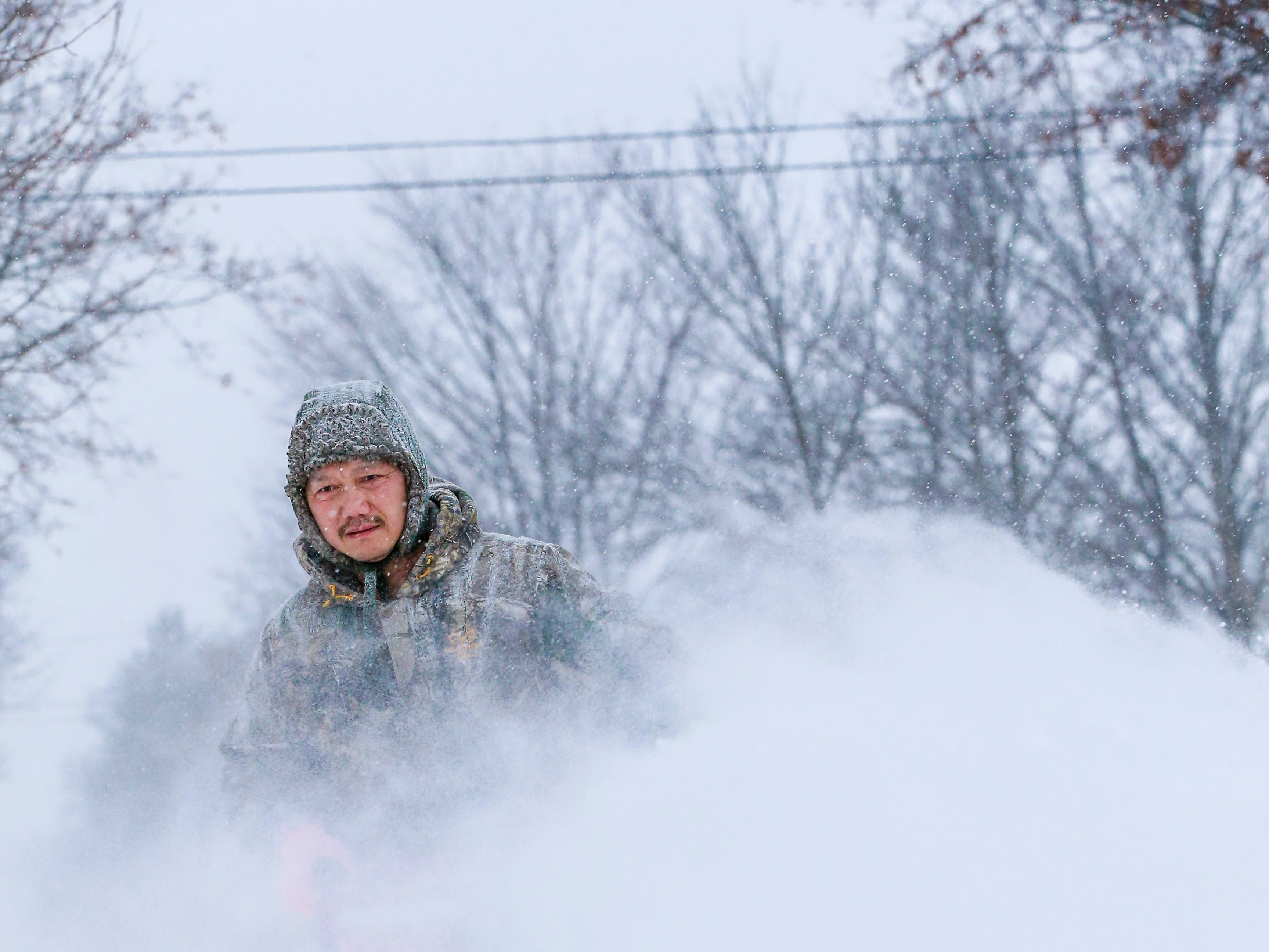 Kangshoua Her checks his way while operating his snowblower on his sidewalk after a snowstorm Monday, Jan. 28, 2019, in Wausau, Wis.