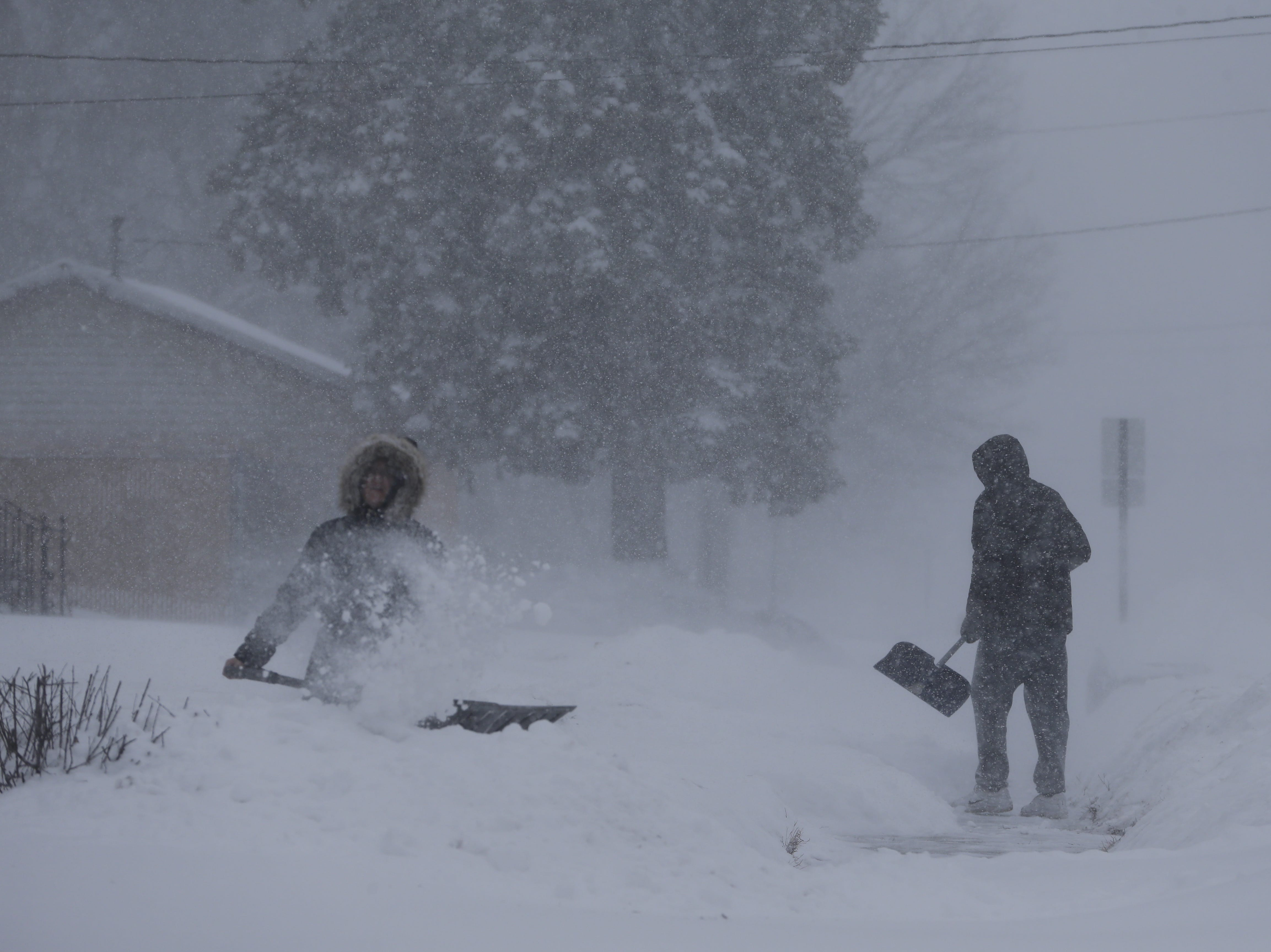 Abby O'Brien and Spencer Couser shovel snow from their sidewalk on the 1100 block of Marshall Street during a snowstorm Monday, January 28, 2019, in Manitowoc, Wis.