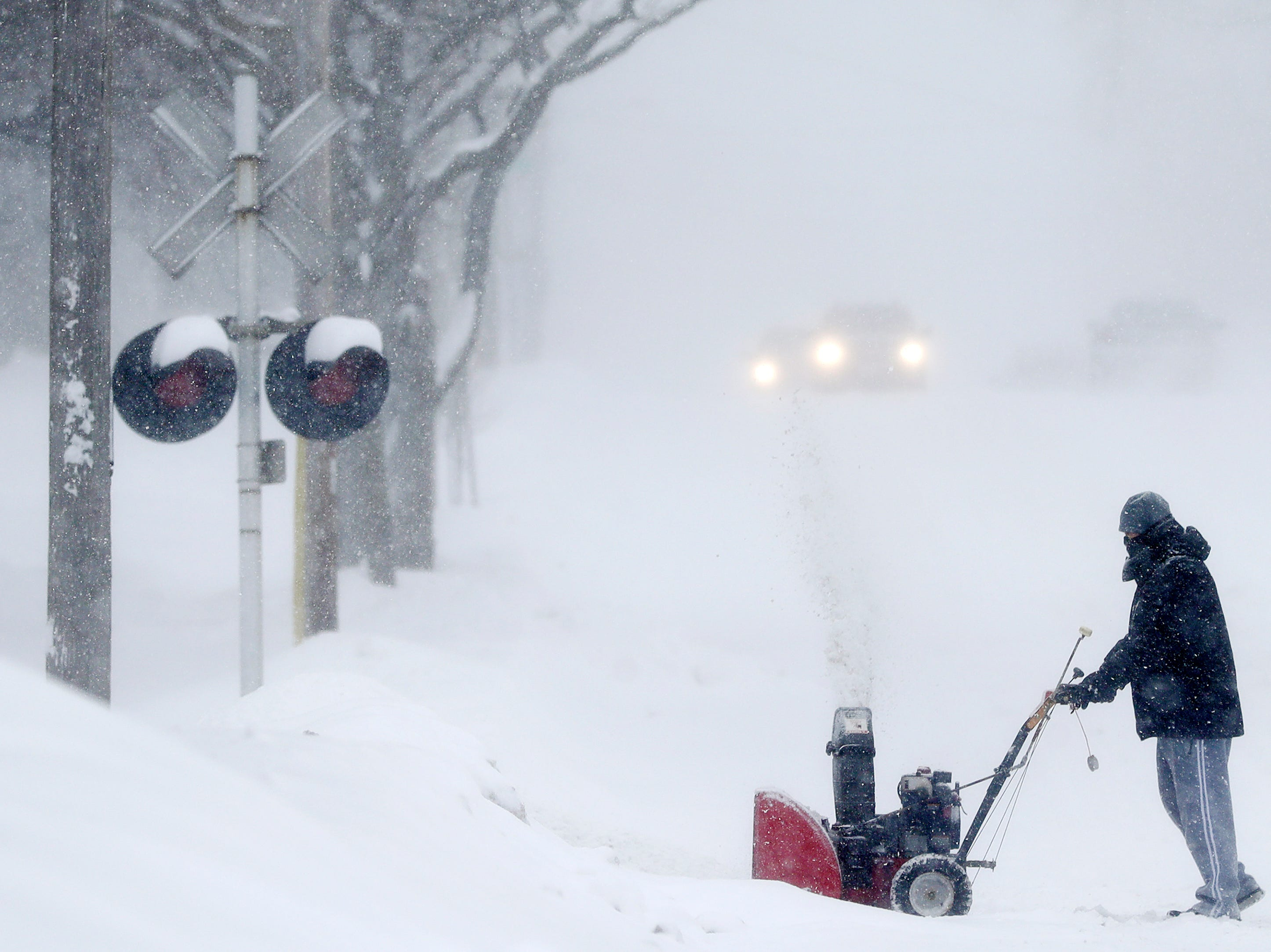 A resident uses a snowblower on his driveway during a snowstorm on Monday, January 28, 2019 in Green Bay, Wis.