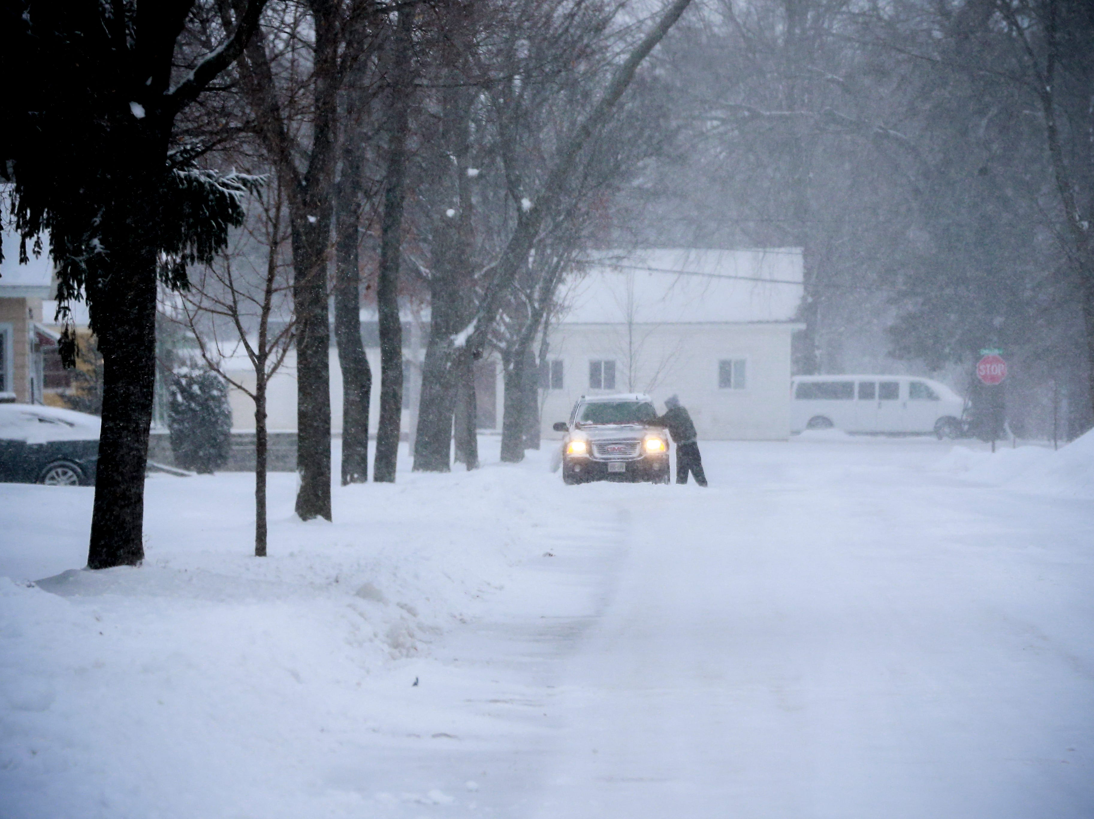 A person seen to clear off snow from his SUV vehicle after a snowstorm Monday, Jan. 28, 2019, in Wausau, Wis.