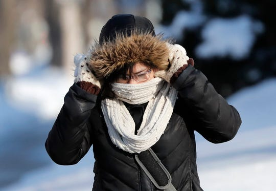 Celeste Reyes, a student at Lawrence University, pulls her hood over her ears while crossing College Avenue on Friday, Jan. 25, 2019, in Appleton, Wis.