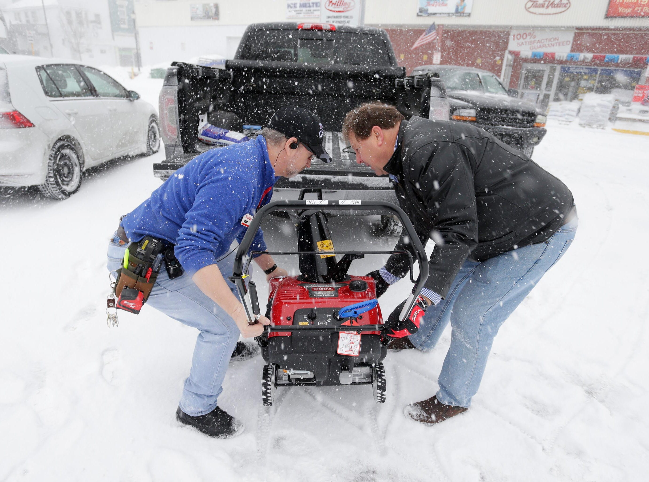 Trilling True Value's Chris Schramm, left, and Greg Parmly, lift a snowblower into a truck for delivery to a customer on Monday, Jan. 28, 2019, in Sheboygan, Wis. Parmly said that his firm sold 15 snowblowers last week due to anticipation from the storm.