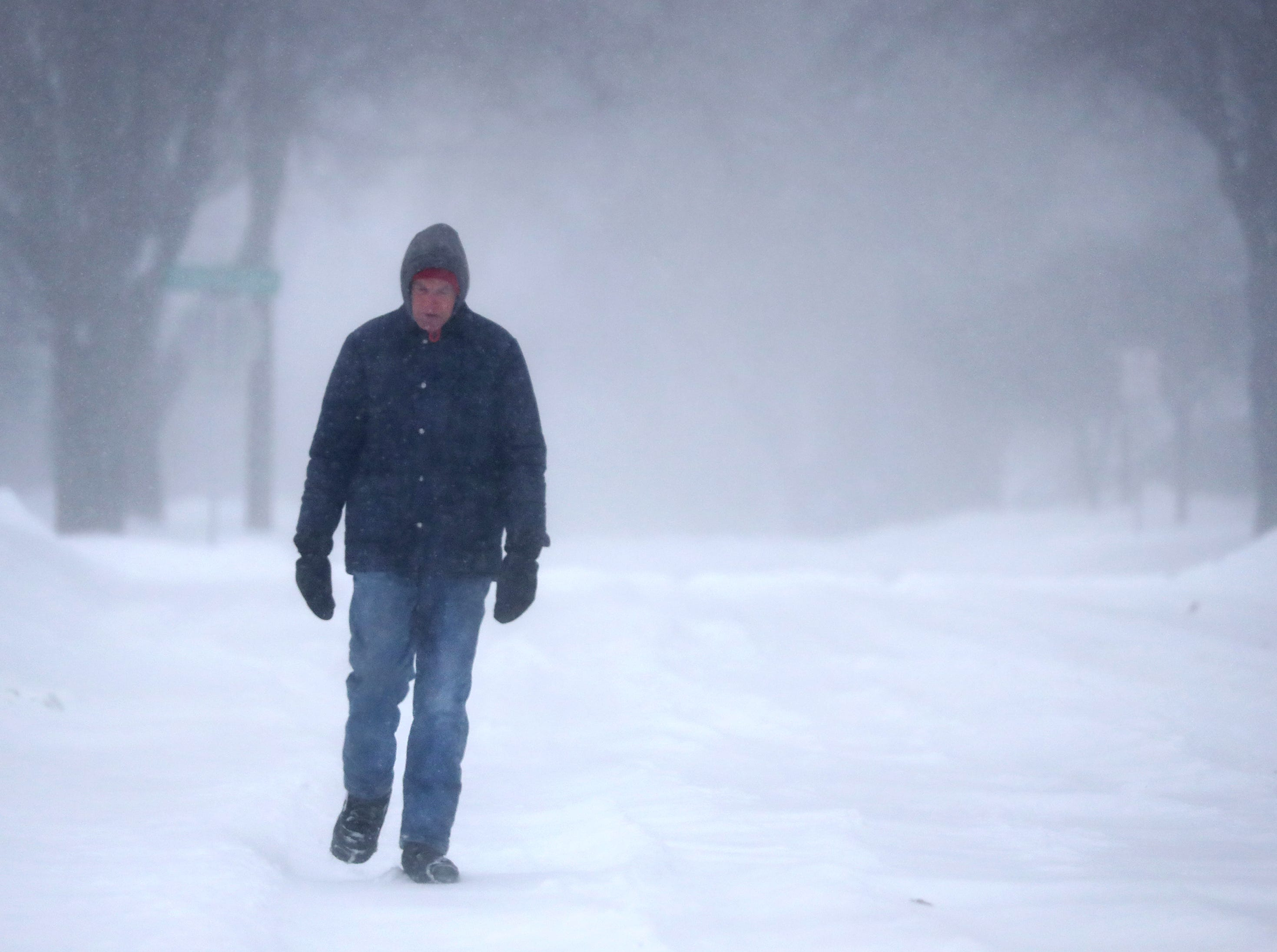 Jim School takes a walk as a winter storm moves through Wisconsin on Monday, January 28, 2019, in Kaukauna, Wis.