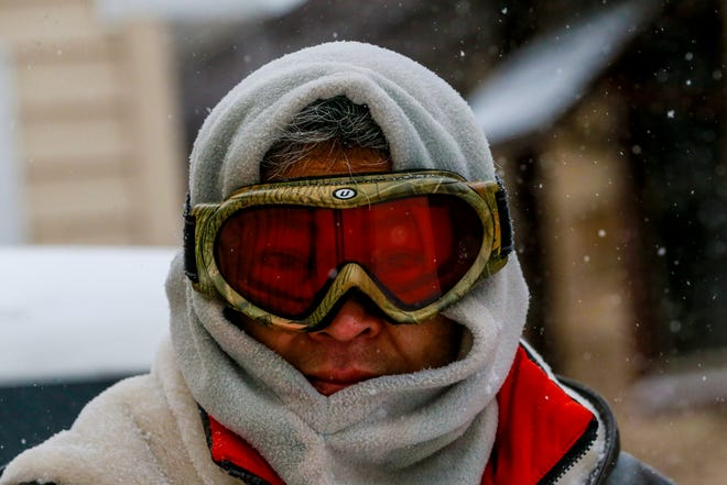 Vichai Gillette gets bundle up with hoodie and ski goggle to clear snow off from his property Monday, Jan. 28, 2019, in Wausau, Wis.