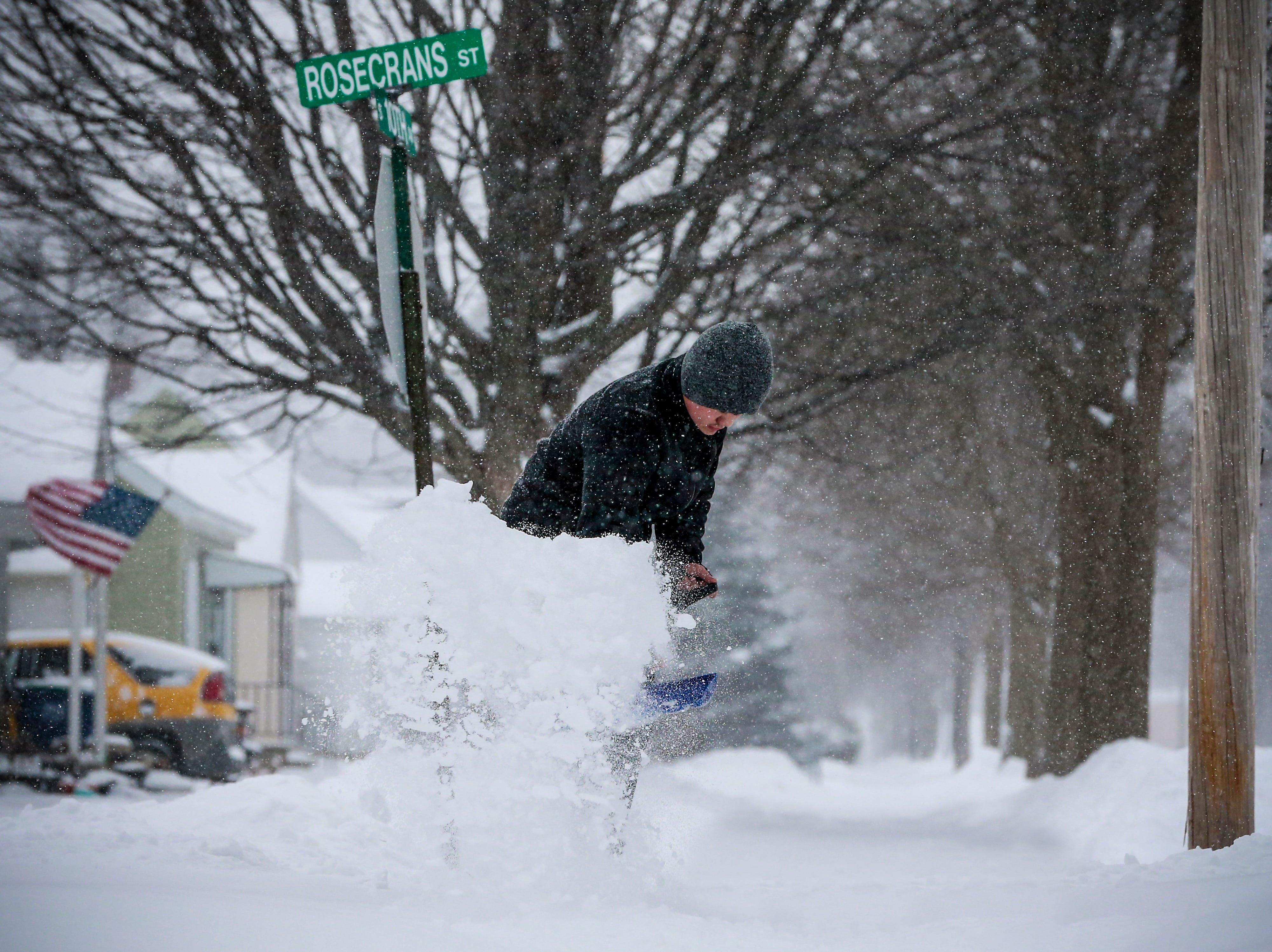 Fong Her shoves snow off his sidewalk after a snowstorm Monday, Jan. 28, 2019, in Wausau, Wis.