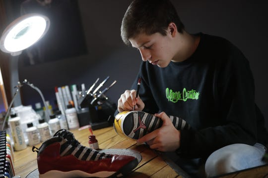Cody Schoeni, a junior at Omro High School, paints a pair of shoes for Iowa State basketball player (and Oshkosh North grad) Tyrese Haliburton at his home in late January. You can see Schoeni's work on Instagram @kingscustom_.