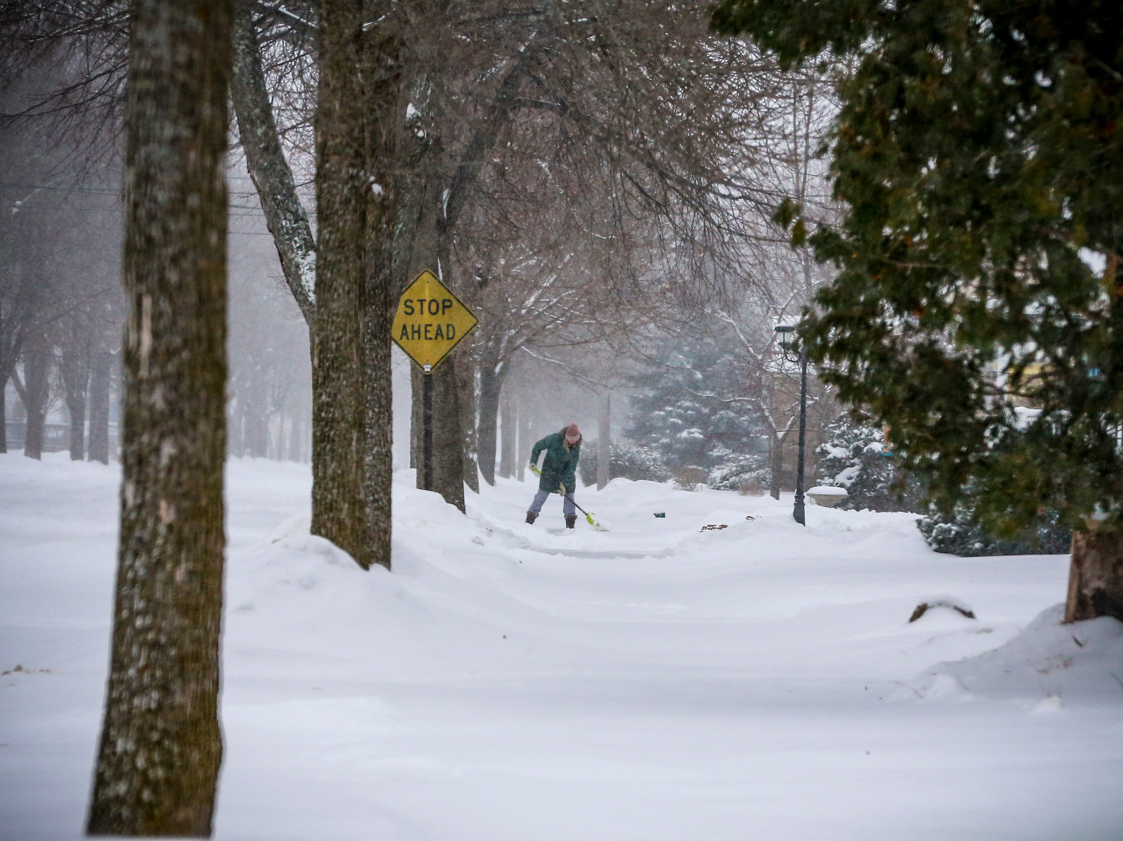 A resident shoveling snow on her property after a snowstorm Monday, Jan. 28, 2019, in Wausau, Wis.