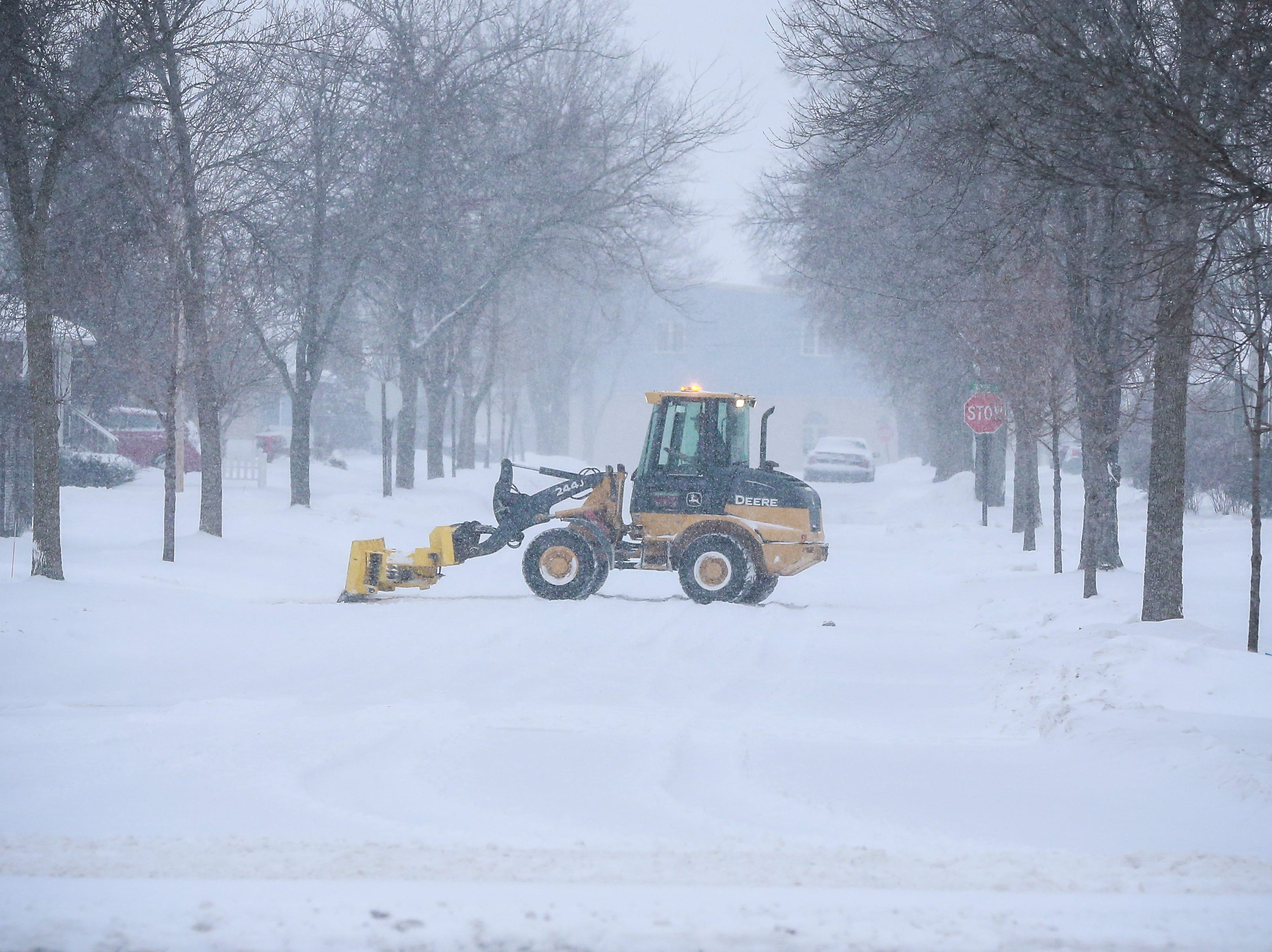 A construction vehicle clears snow on a property after a snowstorm Monday, Jan. 28, 2019, in Wausau, Wis.