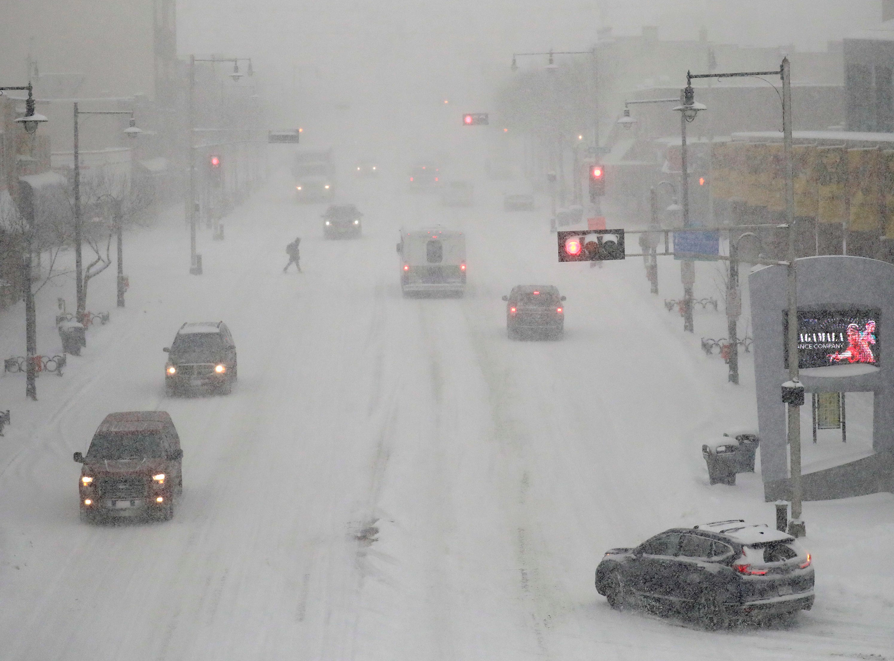 A lone pedestrian crosses College Avenue as traffic moves slowly along College Avenue during a snowstorm Wednesday, Jan. 23, 2019, in Appleton, Wis.