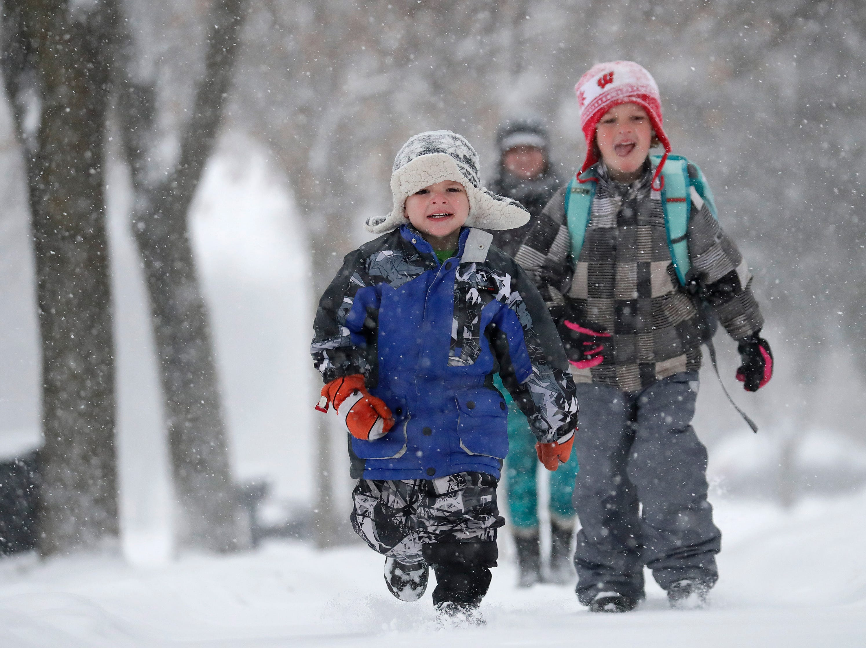 Carter Dench, left, 4, and his brother Darian, 6, enjoy the snowfall as they head to school with their mother Abbie Dench during a snowstorm Wednesday, January 23, 2019, in Appleton, Wis. 