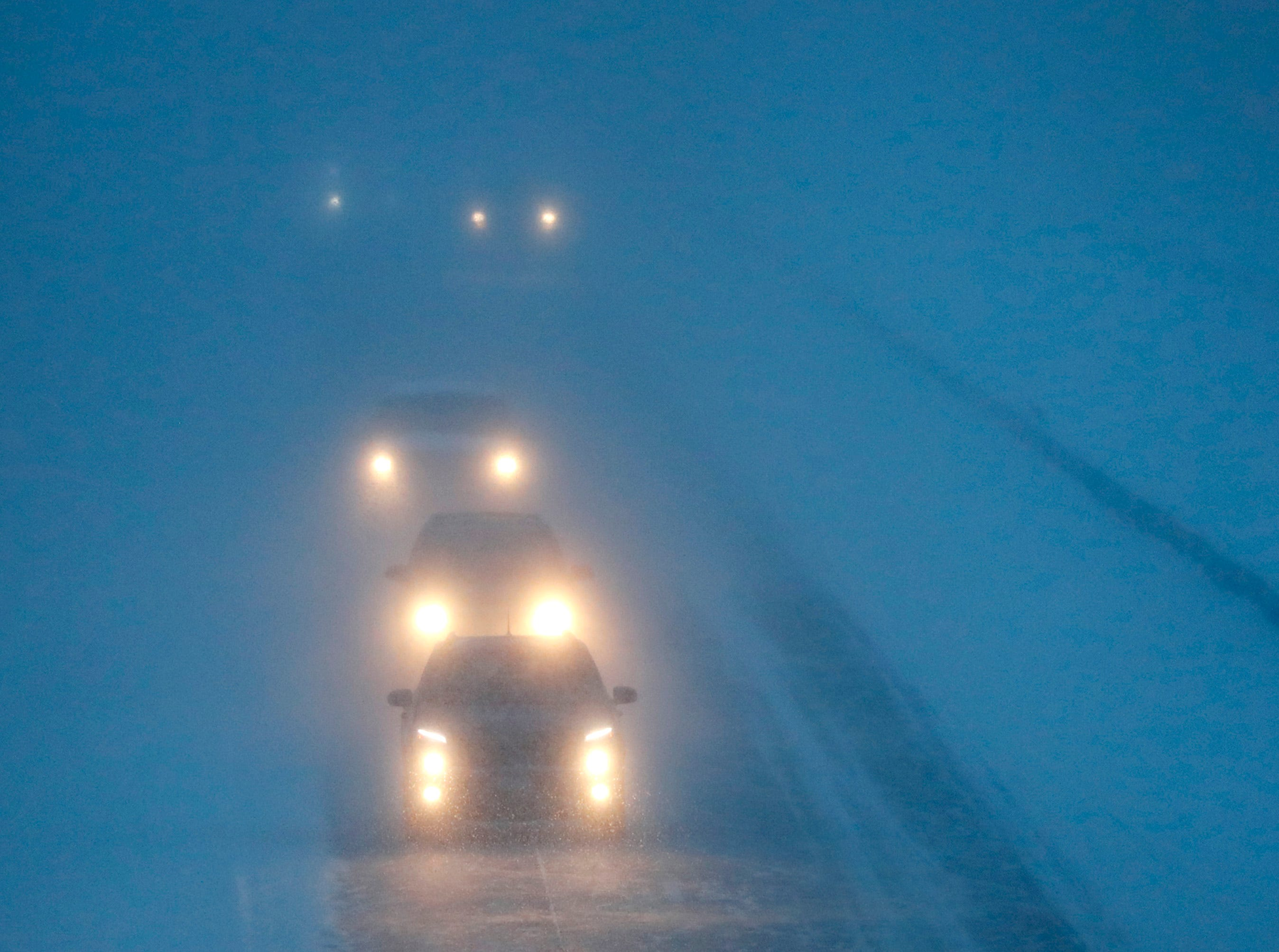 Headlights from morning commuters can be seen through blowing snow as they make their way along 441 during a snowstorm Monday, Jan. 28, 2019, in Appleton, Wis.