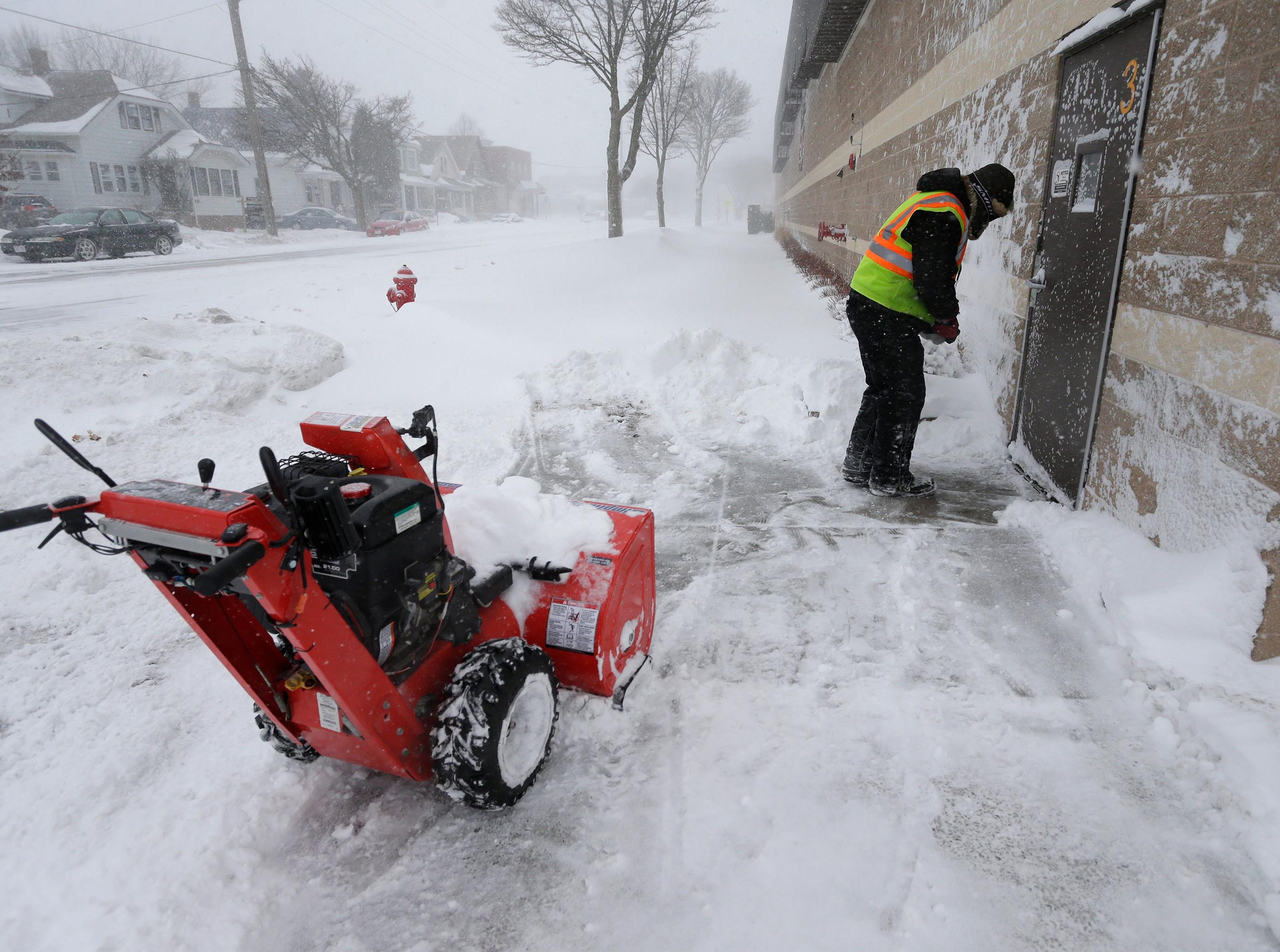 Jim Schwaonek of Paper Box Company shovels snow from around an entrance at the firm, Monday, Jan. 28, 2019, in Sheboygan, Wis.