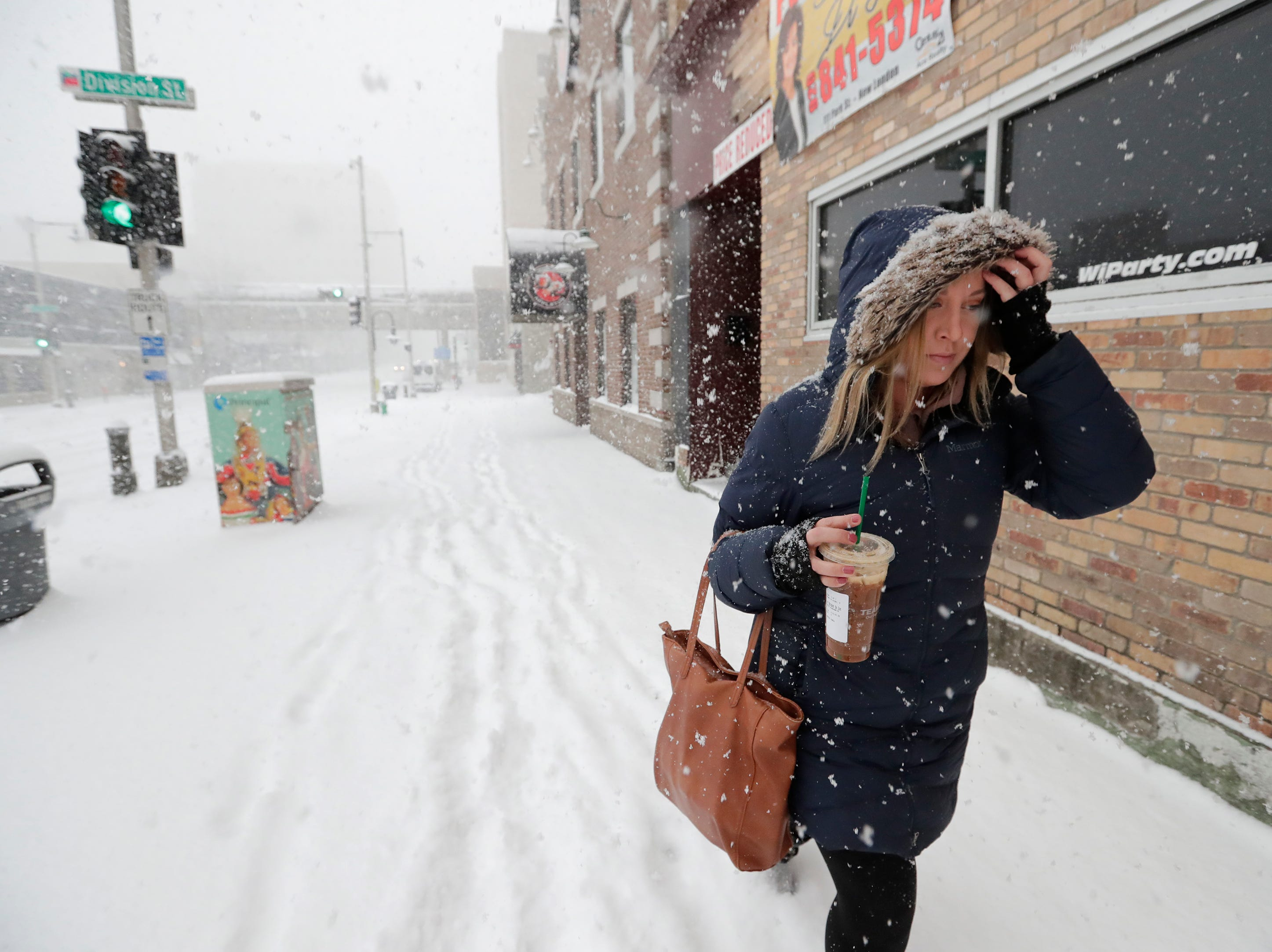Jenna Gutbrod of Greenville braves the blowing wind and snow to head to work at Dealer Inspire during a snowstorm Wednesday, January 23, 2019, in downtown Appleton, Wis. 