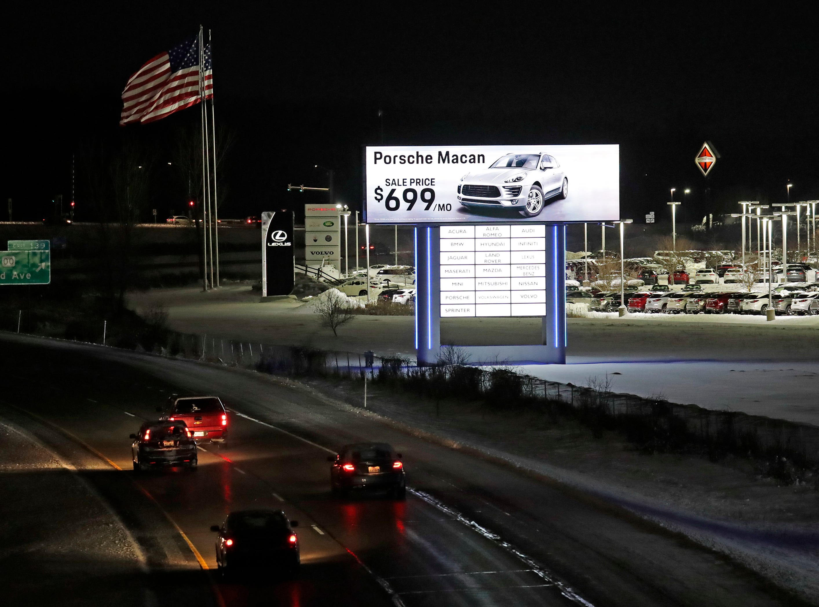 Bergstrom Automotive signs are illuminated along I-41 Wednesday, Jan. 23, 2019, in Grand Chute, Wis. The Department of Transportation says they violate state and federal law.