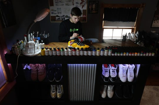 Omro High School junior Cody Schoeni works on a custom painted pair of shoes for Iowa State basketball player Tyrese Haliburton in late January. Schoeni has been painting shoes for about a year and has designed and painted shoes for Haliburton and Thon Maker of the Milwaukee Bucks.