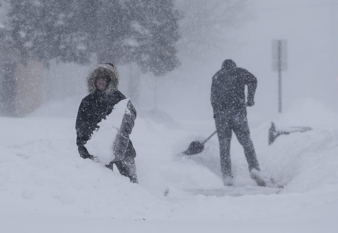Abby O'Brien, left, and Spencer Couser shovel snow from their sidewalk during a January snowstorm in Manitowoc.