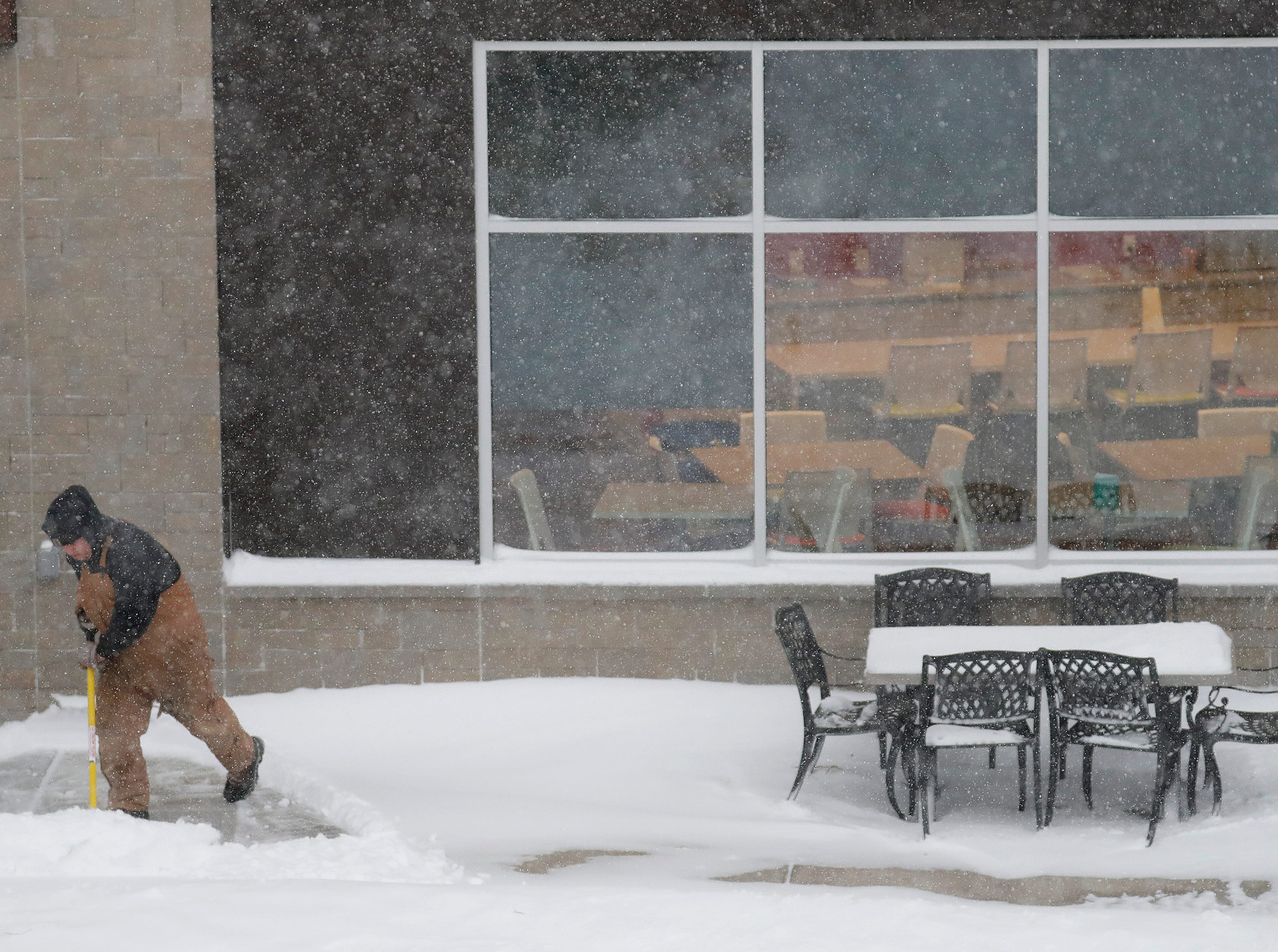 Taylor Vandermoss of Kaukauna shovels snow from a walkway at Thrivent Federal Credit Union during a snowstorm Monday, Jan. 28, 2019, in Appleton, Wis.
