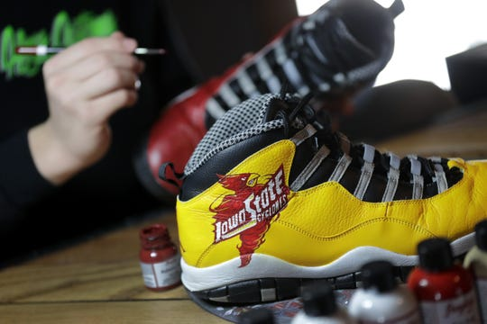Cody Schoeni, a junior at Omro High School, paints a pair of shoes for Iowa State basketball player Tyrese Haliburton at his home in Omro in late January.