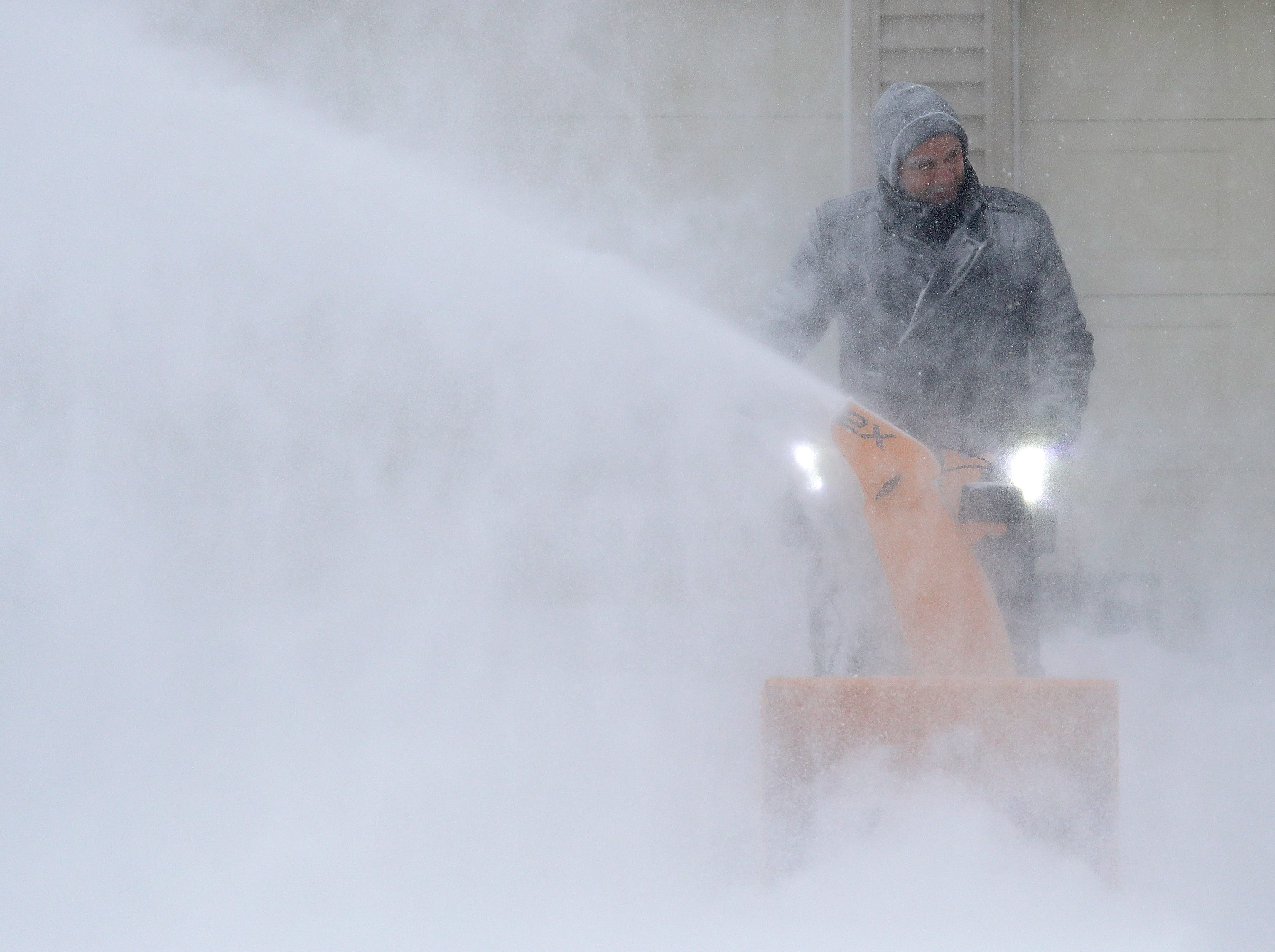 David Liebhard fights windy conditions as he snow blows his driveway during a snowstorm Monday, Jan. 28, 2019, in Appleton, Wis.