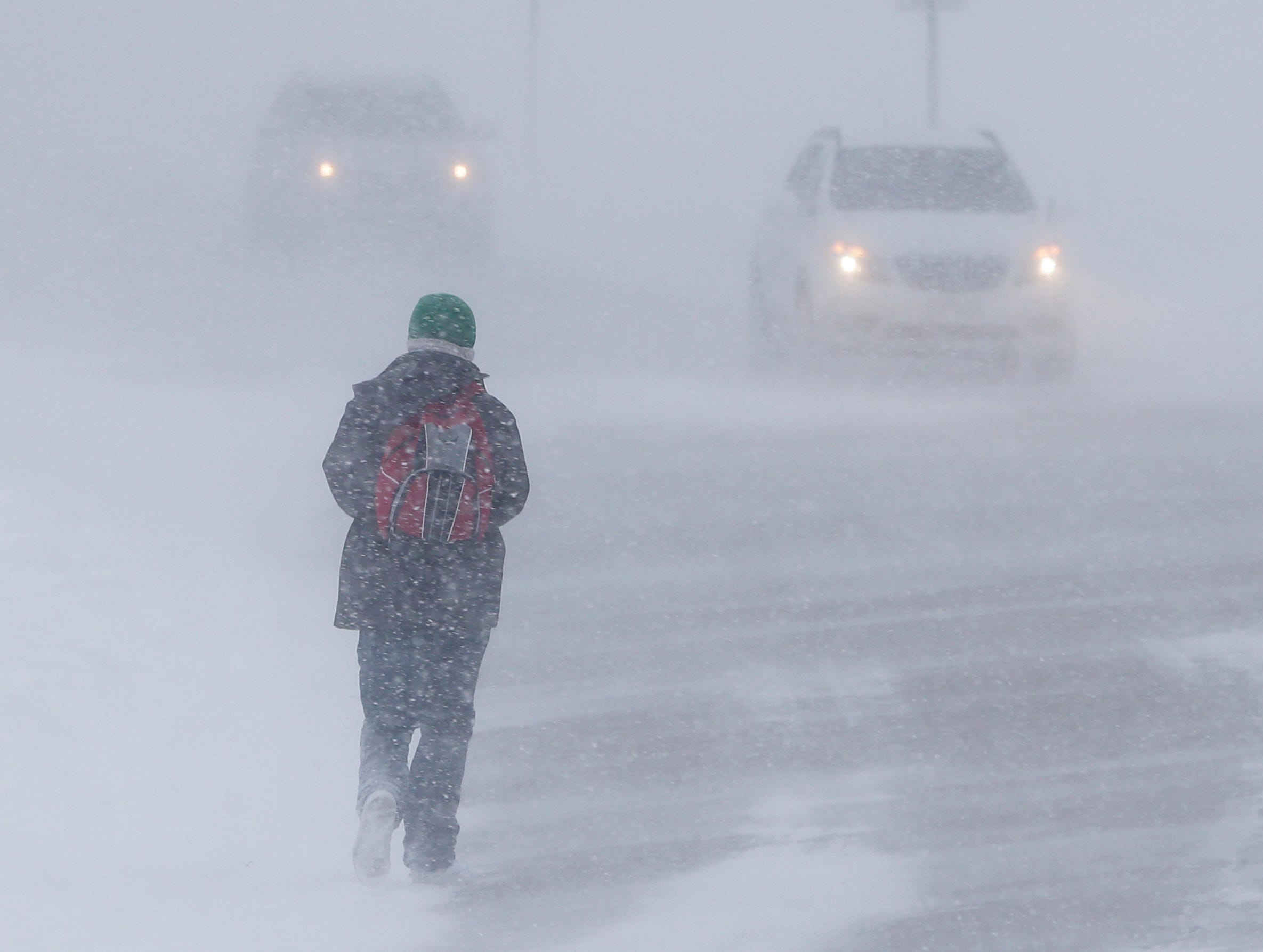 A pedestrian walks north on Maritime Drive near Lake Michigan in whiteout conditions during a snowstorm Monday, Jan. 28, 2019, in Manitowoc, Wis.