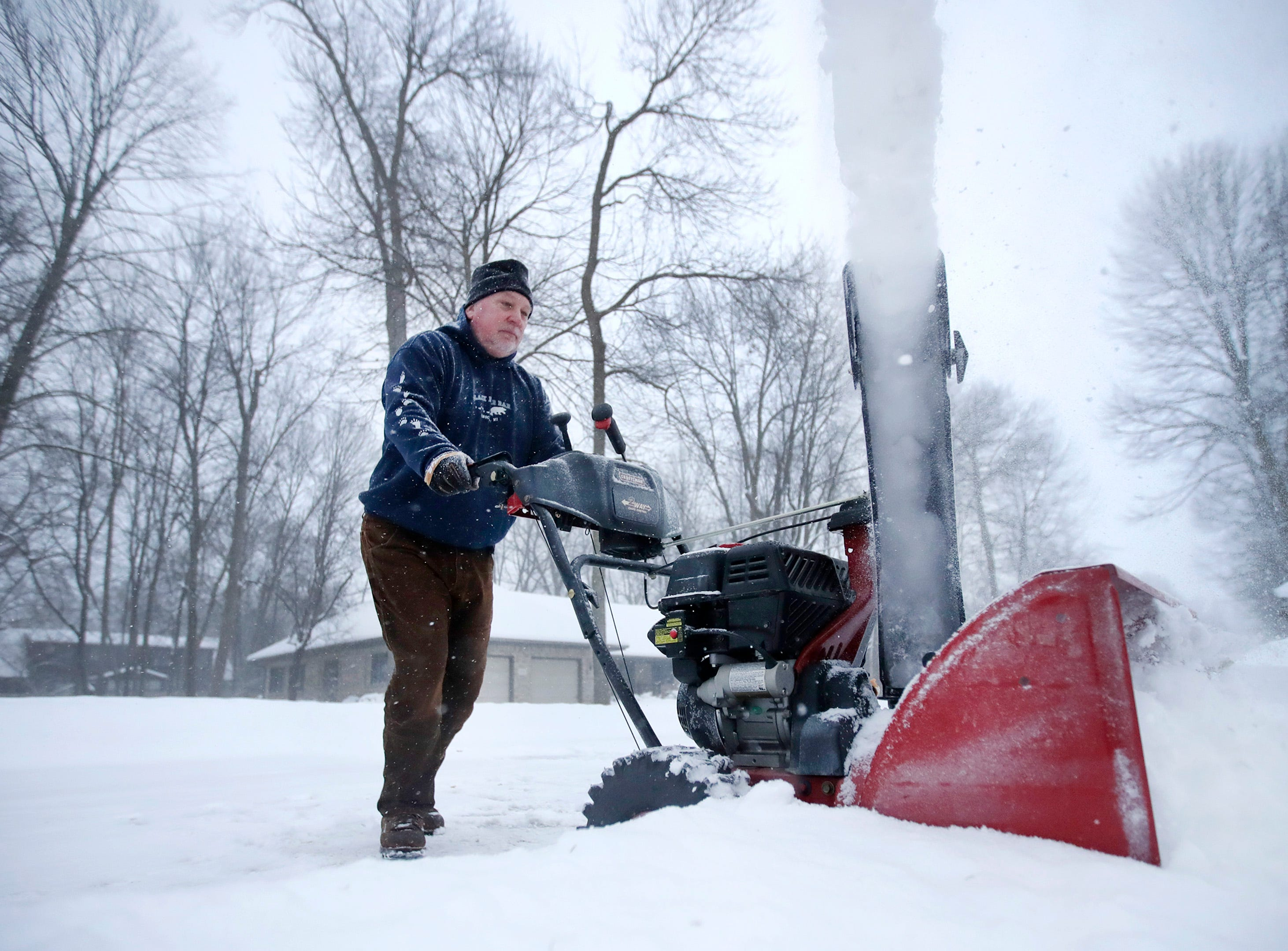 Jim Abendrota, of Appleton, sends a stream of snow into his yard as he clears his driveway Monday, Jan. 28, 2019, in Appleton, Wis.