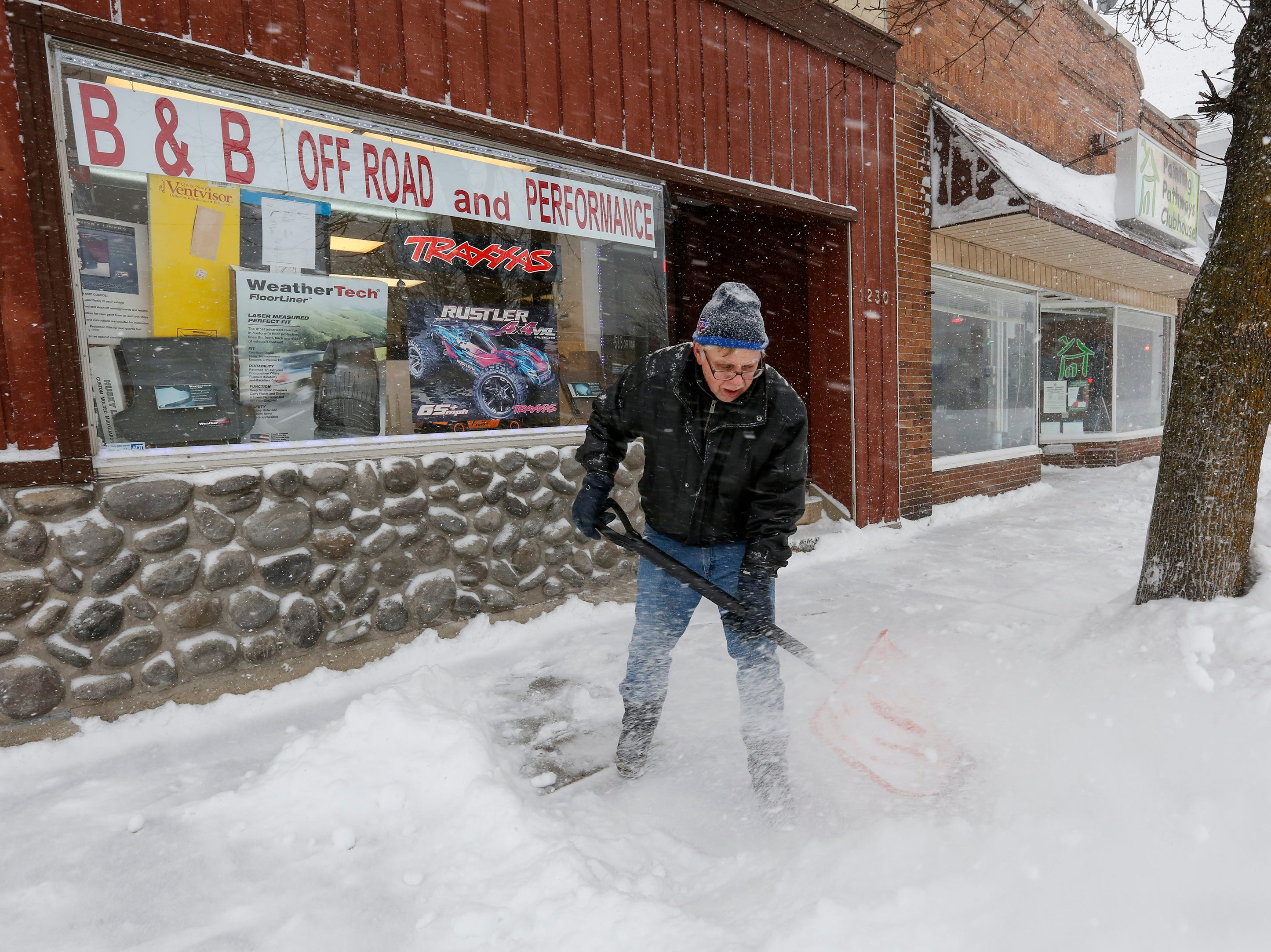 Bill Stalvey, of Manitowoc, clears the sidewalk in front of his shop, B & B Off Road and Performance RC, during a winter storm Monday, Jan. 28, 2019, in Manitowoc, Wis.